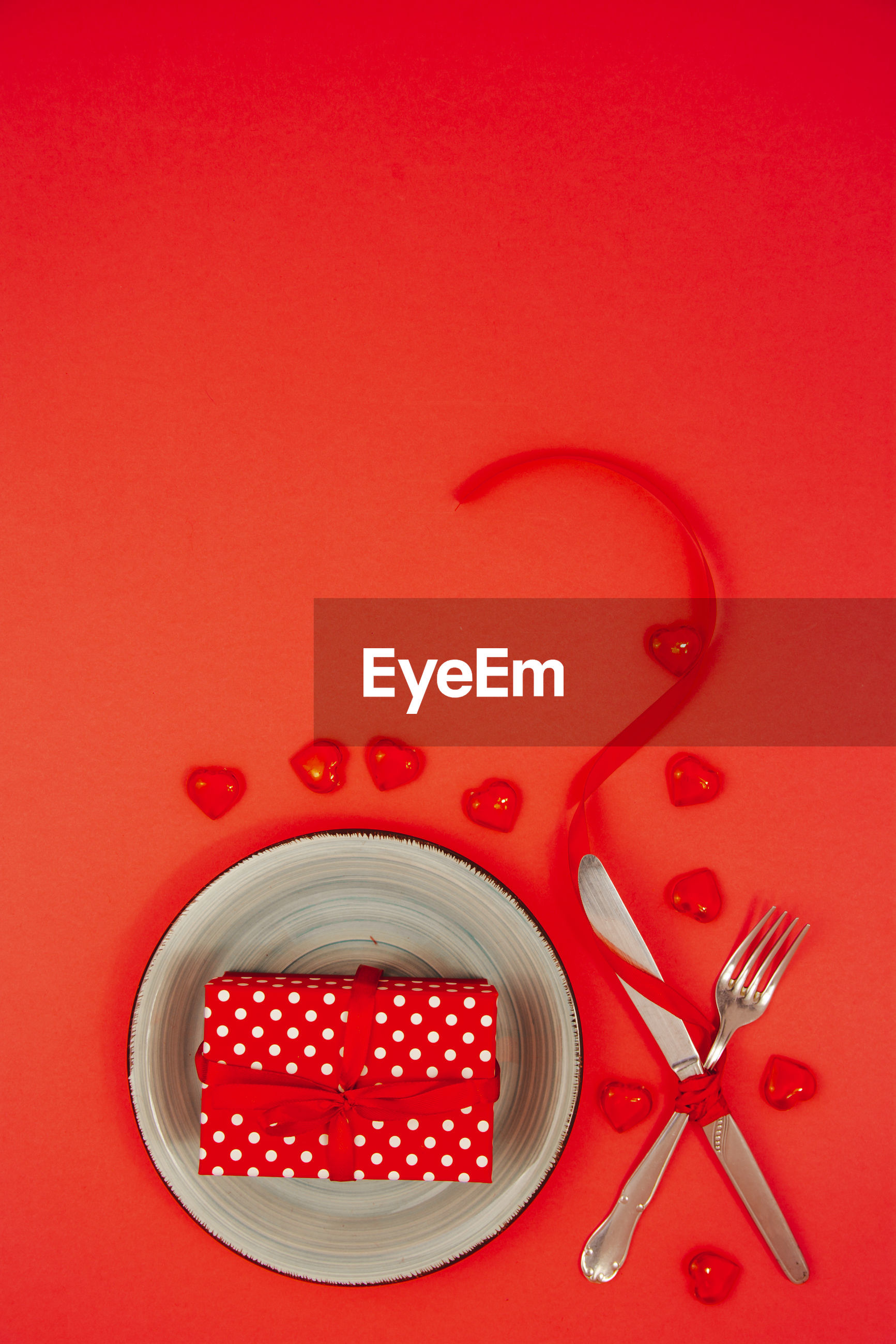 Directly above shot of gift in bowl with cutlery over red background