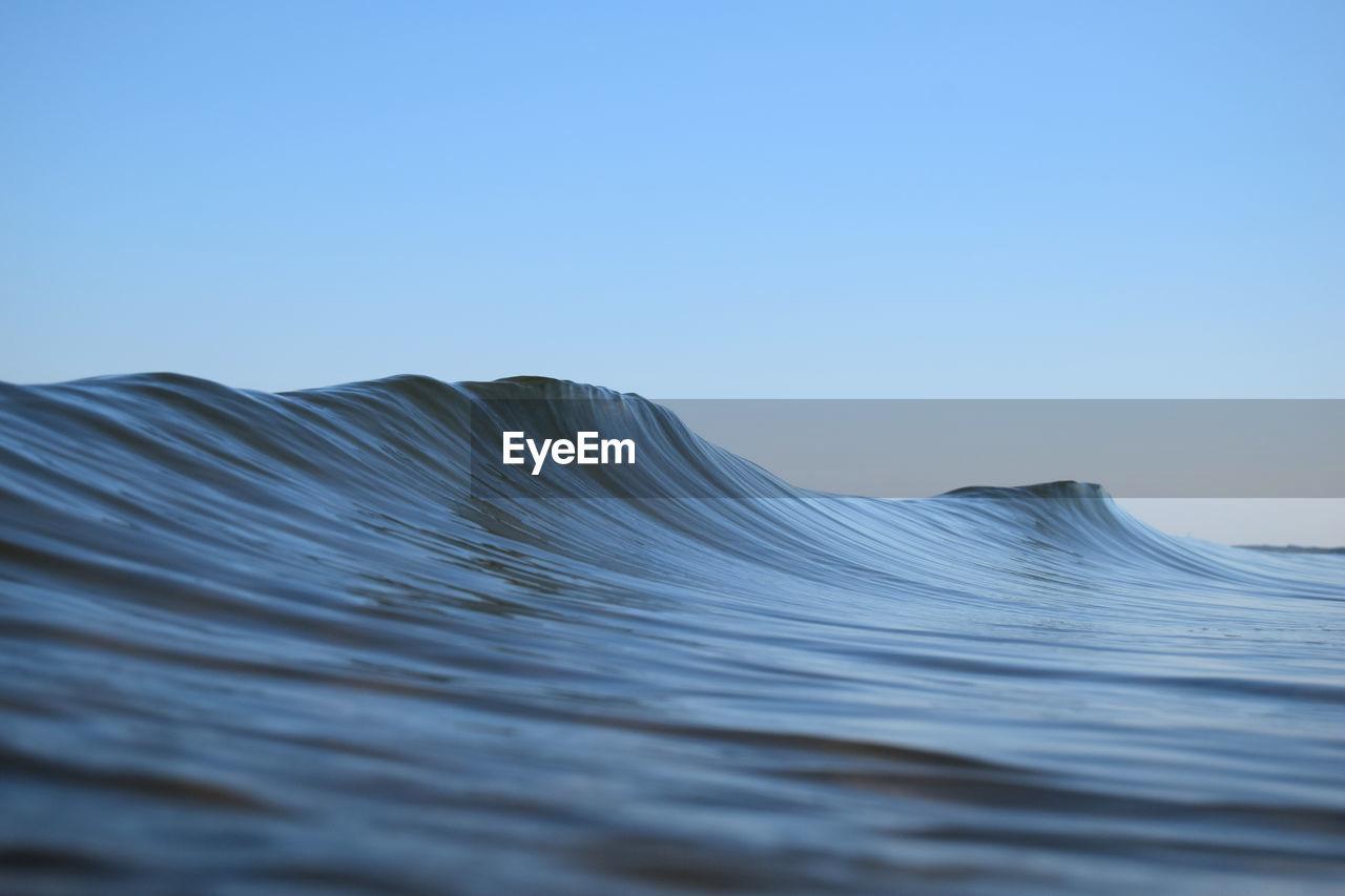 Sea waves against clear blue sky