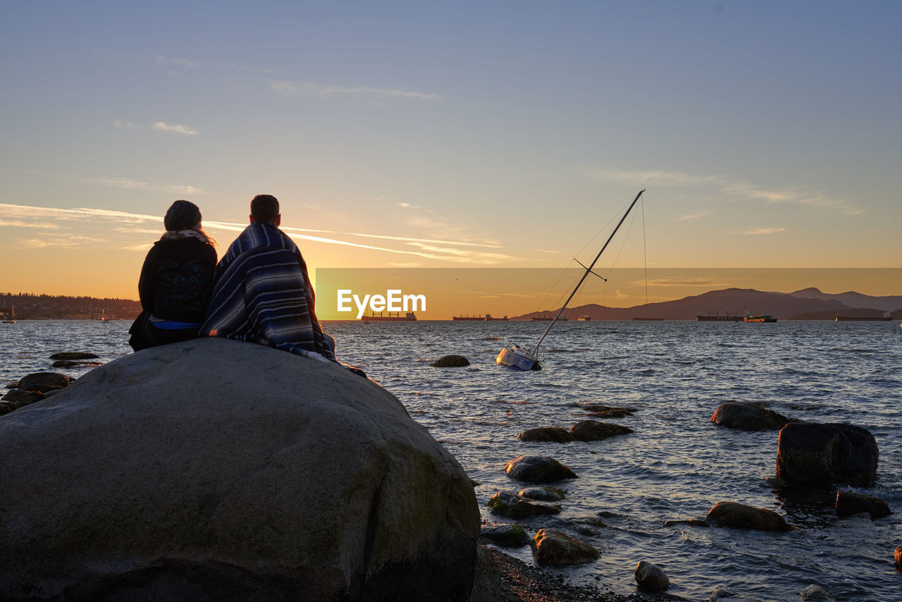 Couple on rock by sea against sky during sunset
