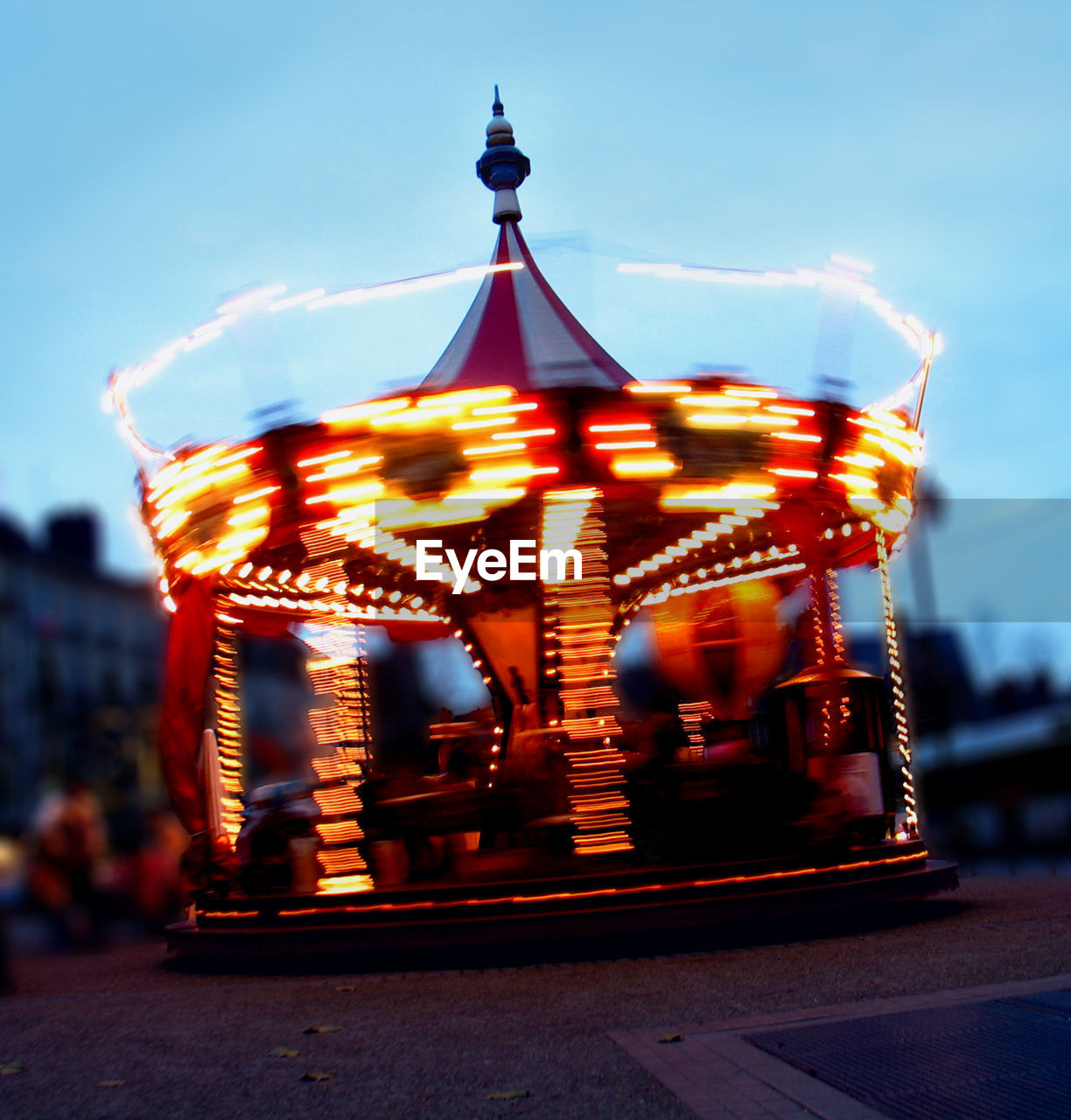 sky, carousel, illuminated, arts culture and entertainment, motion, amusement park ride, amusement park, blurred motion, architecture, no people, nature, focus on foreground, built structure, outdoors, dusk, building exterior, merry-go-round, day, long exposure, cloud - sky