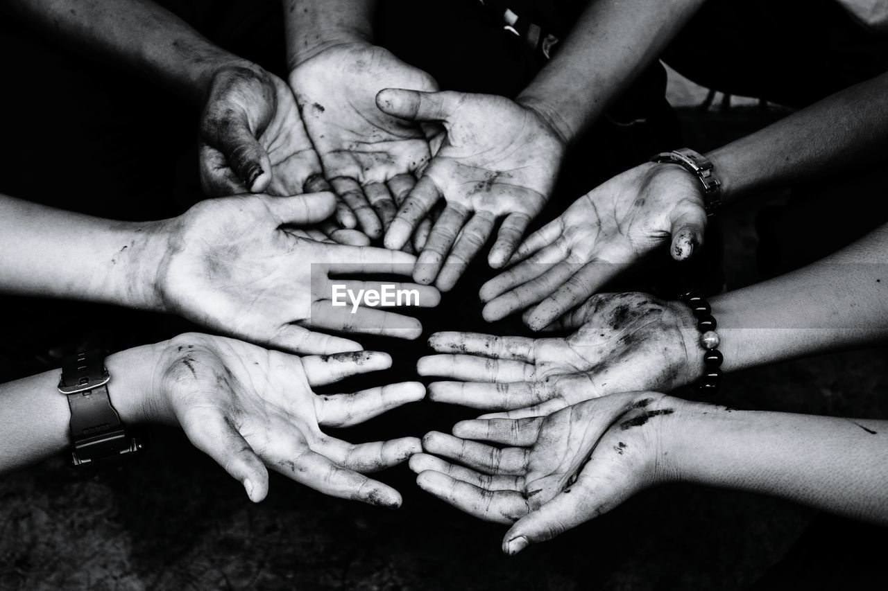 Cropped image of friends showing dirty hands