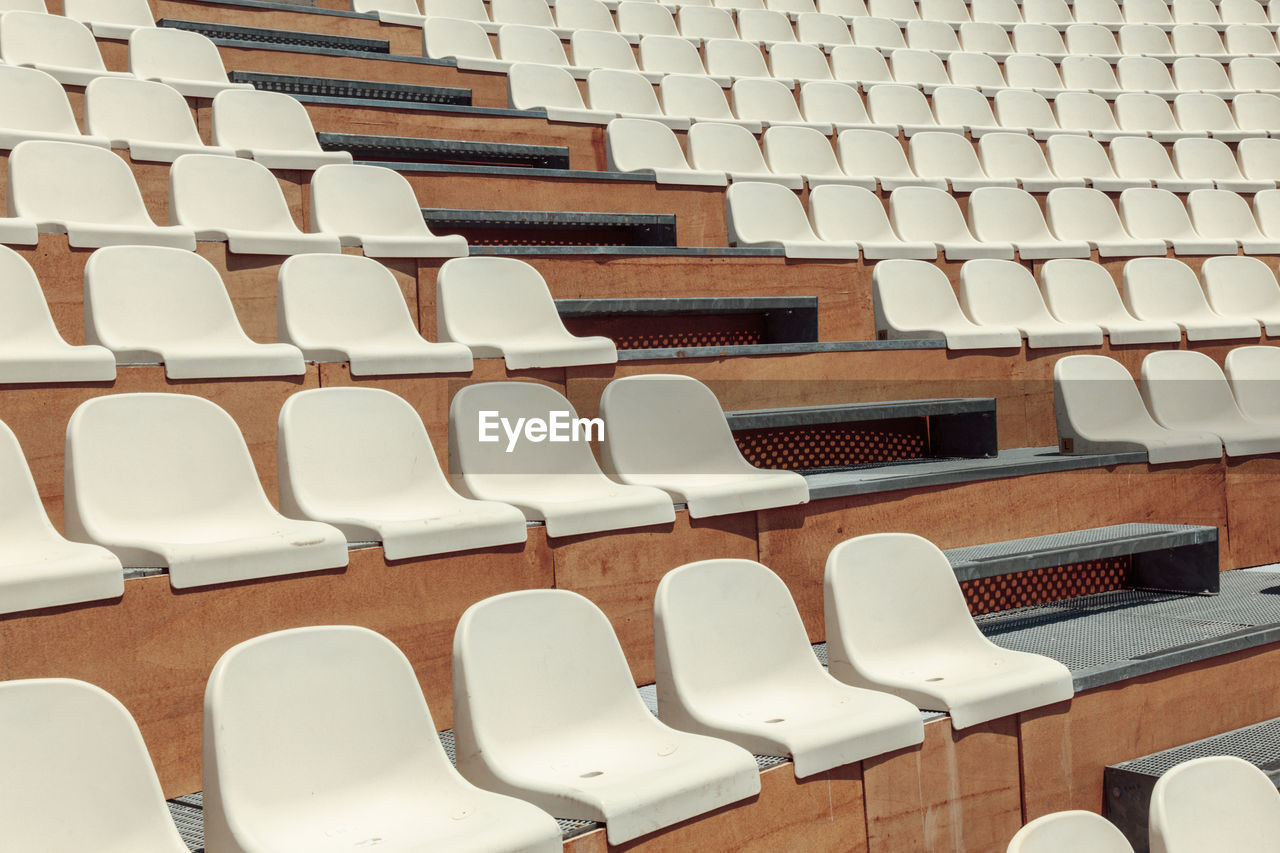 seat, chair, in a row, absence, empty, no people, repetition, architecture, arrangement, large group of objects, built structure, side by side, order, arts culture and entertainment, indoors, high angle view, auditorium, white color, day, table