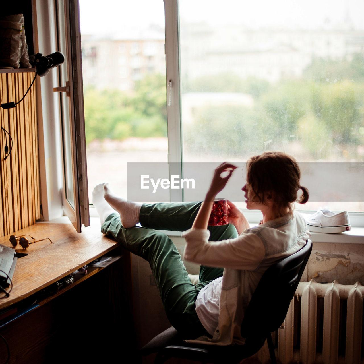 Woman relaxing on window