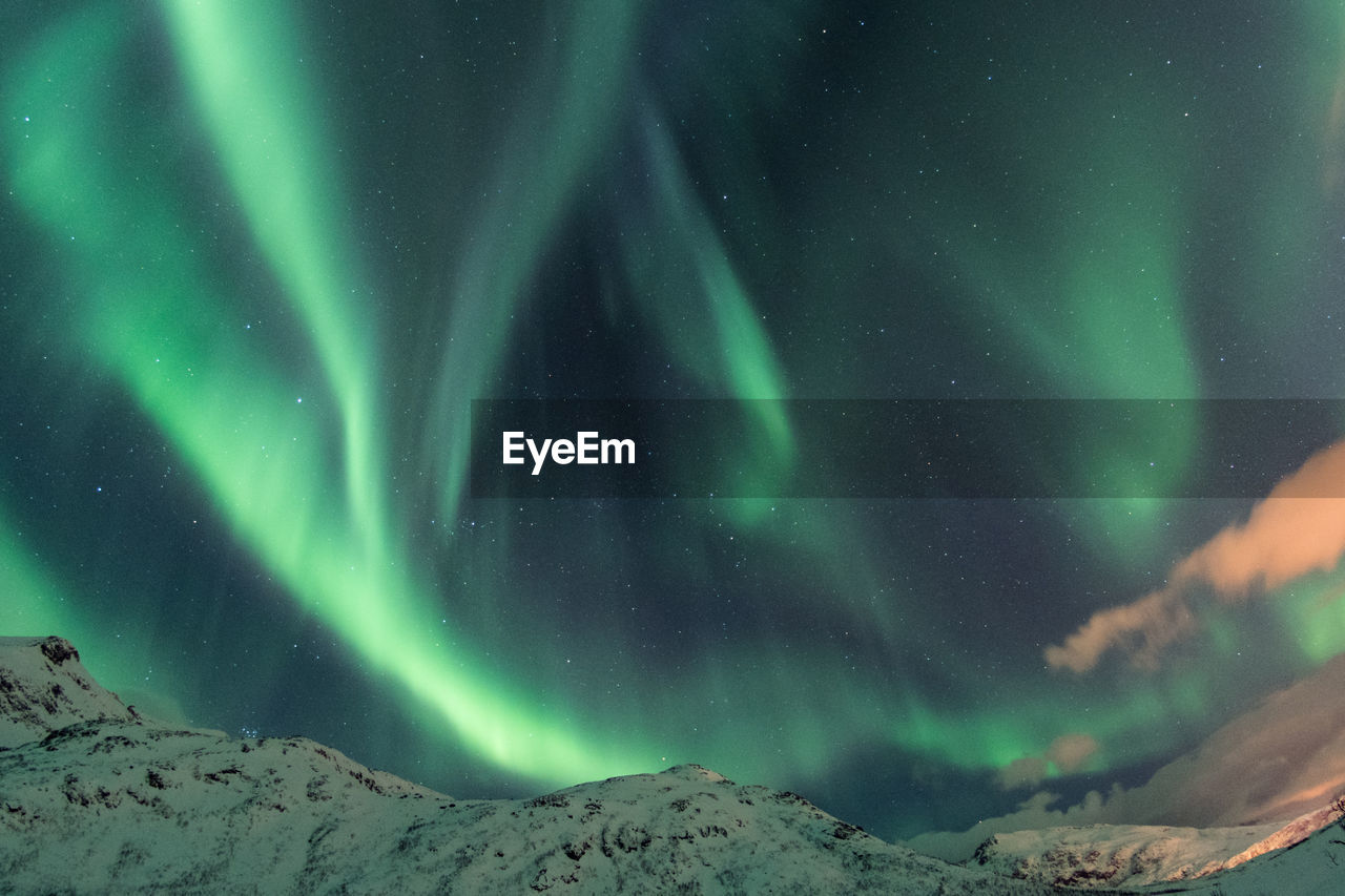 Scenic View Of Aurora Polaris Above Snowcapped Mountains Against Sky At Night