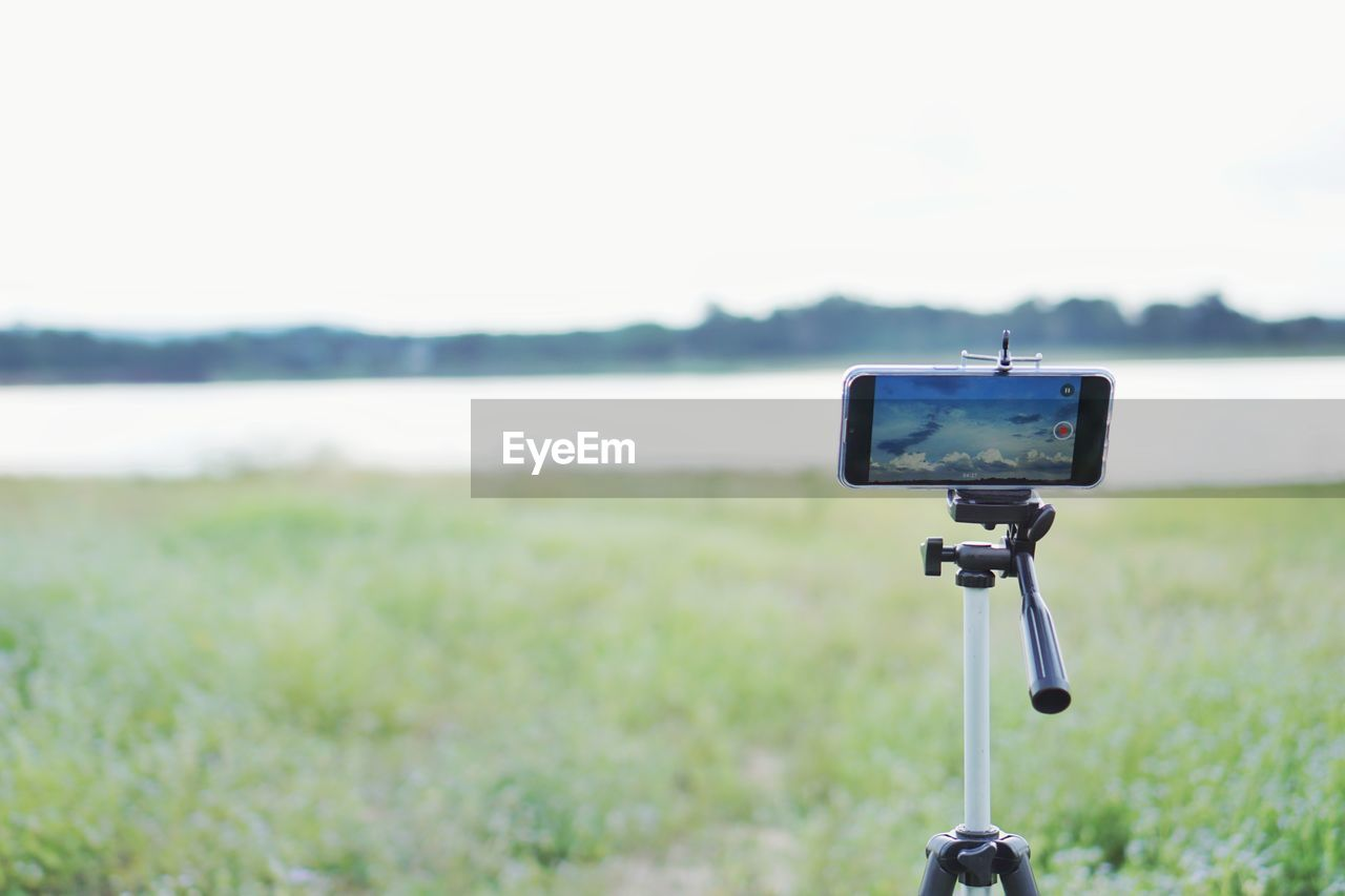 focus on foreground, land, technology, day, field, nature, grass, photography themes, no people, sky, plant, landscape, close-up, copy space, environment, outdoors, beauty in nature, water, tranquility, communication, digital camera
