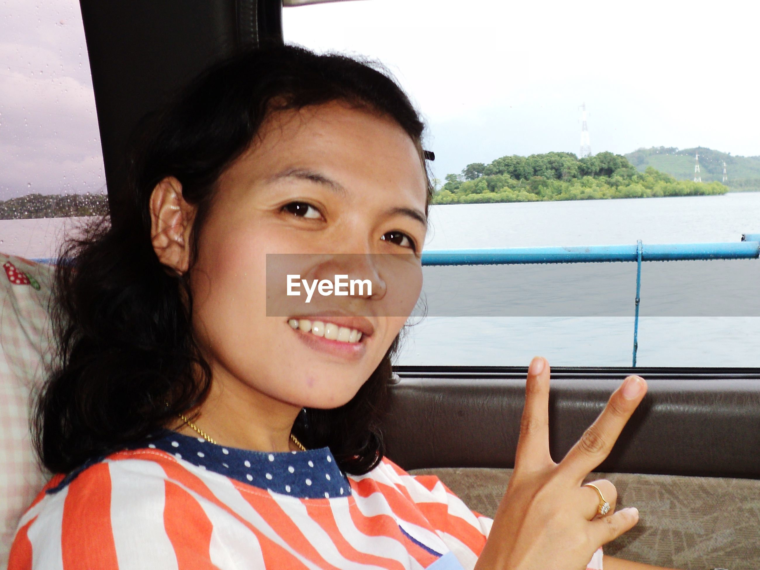 Portrait of smiling young woman gesturing while sitting in car against river