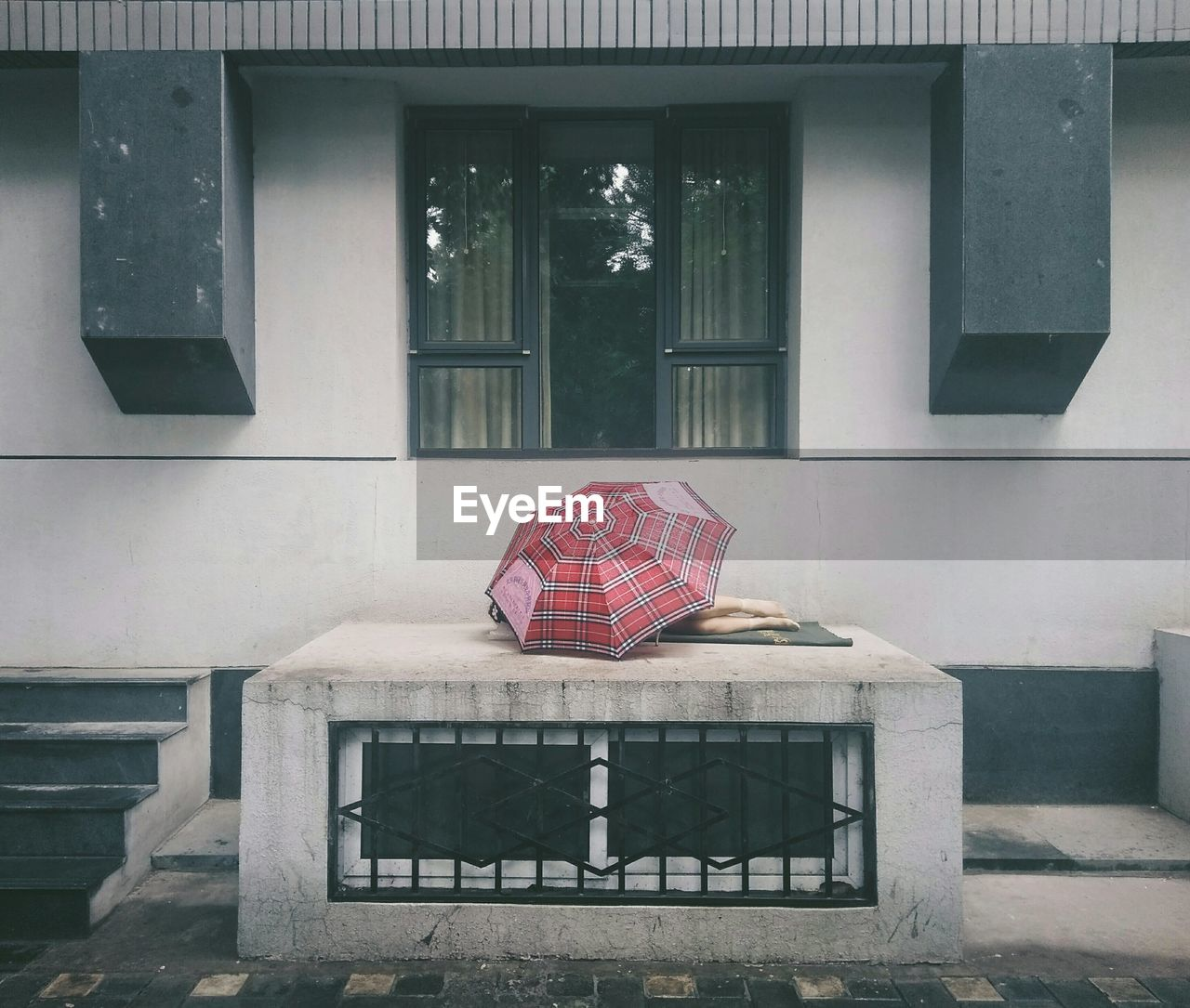 Homeless Person Sleeping Under Umbrella On Porch
