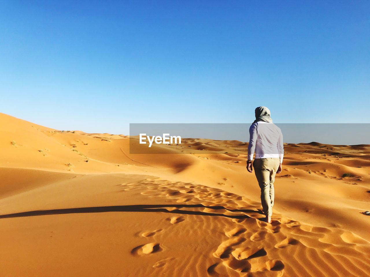 Rear View Of Man Standing On Sand At Desert