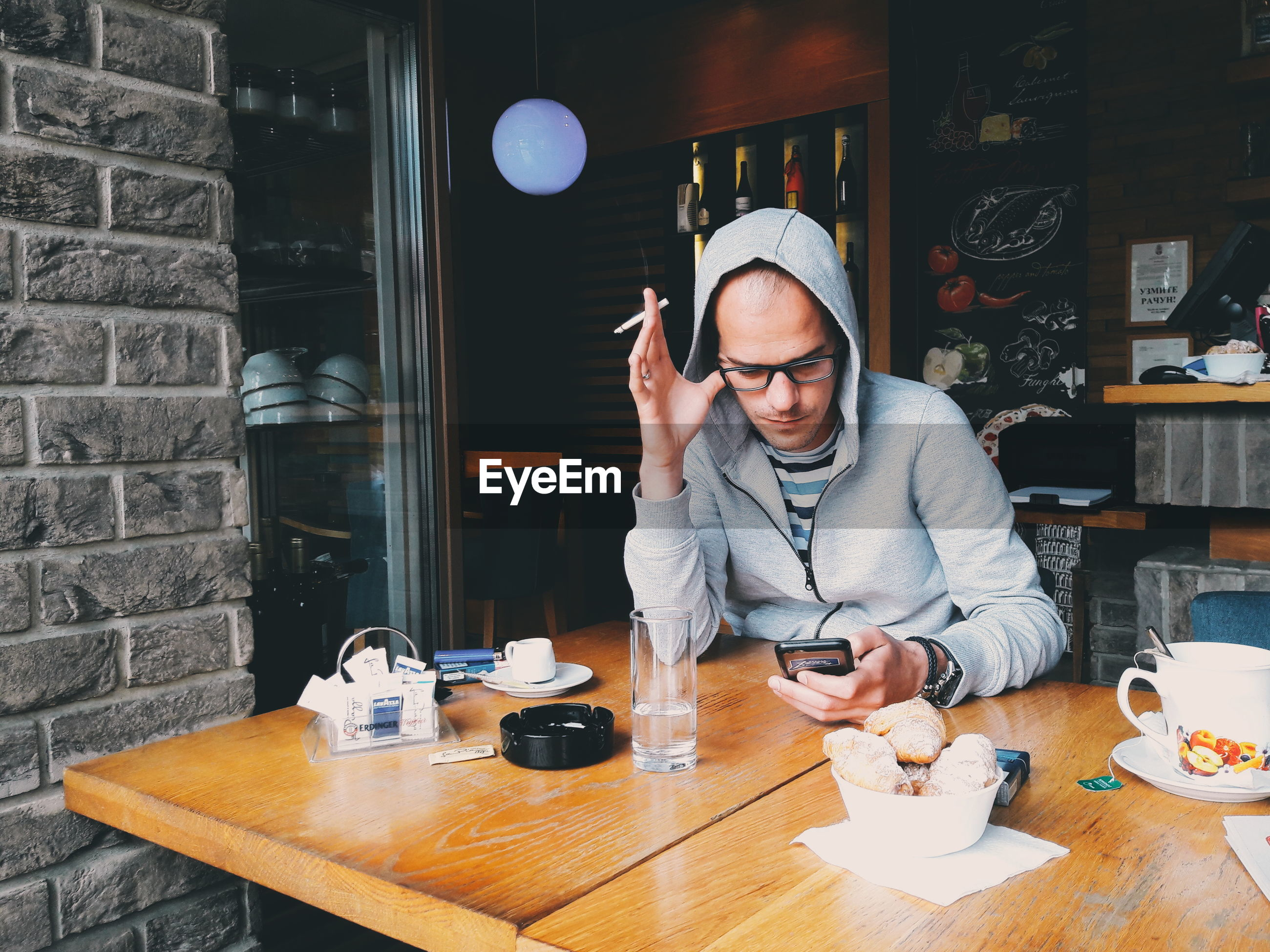 glasses, one person, real people, eyeglasses, table, lifestyles, food and drink, young adult, front view, drink, young men, leisure activity, cup, waist up, mid adult, restaurant, men, holding, adult