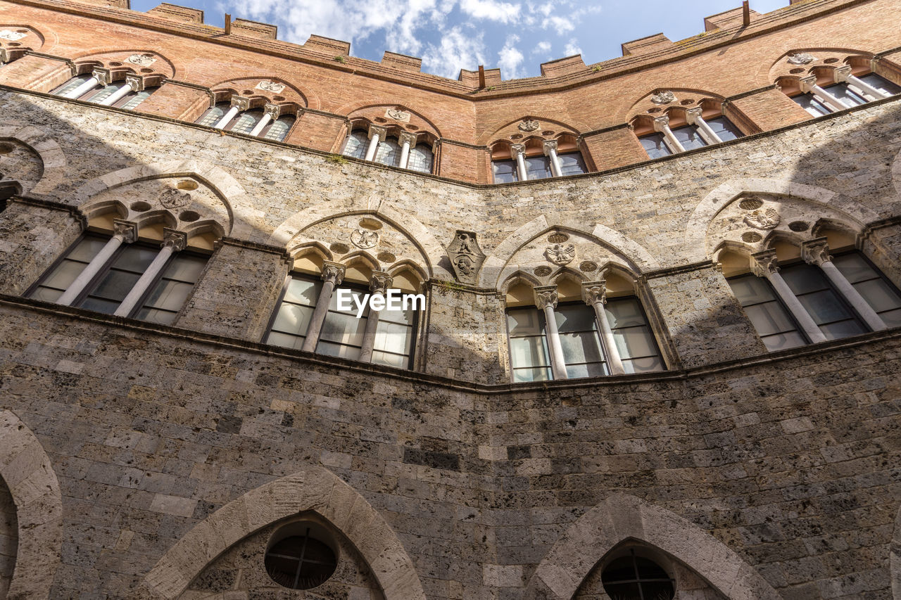 low angle view, built structure, architecture, building exterior, window, arch, building, history, the past, no people, day, sky, travel destinations, cloud - sky, outdoors, old, nature, travel, wall, city, ornate