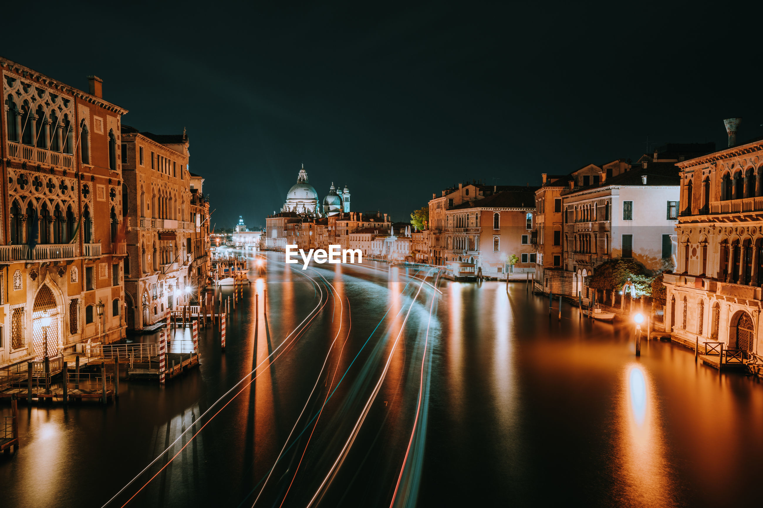 Light trails on river amidst illuminated buildings in city at night