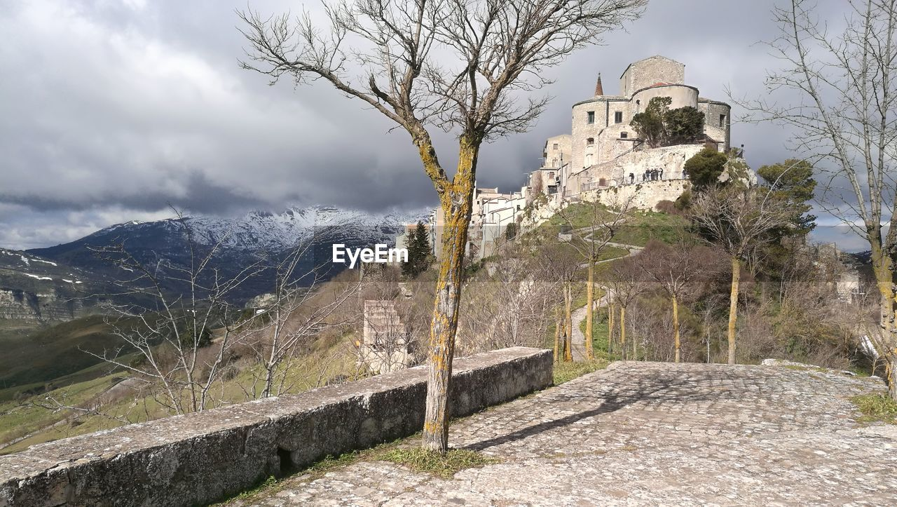 architecture, tree, built structure, sky, plant, building exterior, mountain, history, the past, nature, day, building, travel destinations, religion, wall, no people, travel, place of worship, belief, tourism, outdoors, stone wall