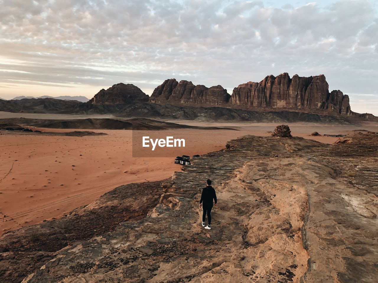 High angle view of man standing on rock formation looking at arid landscape
