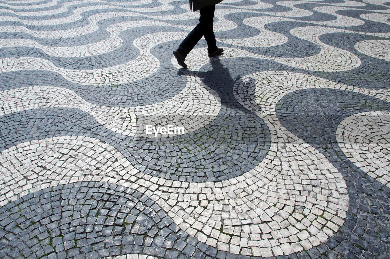 Low section of man walking on cobblestone