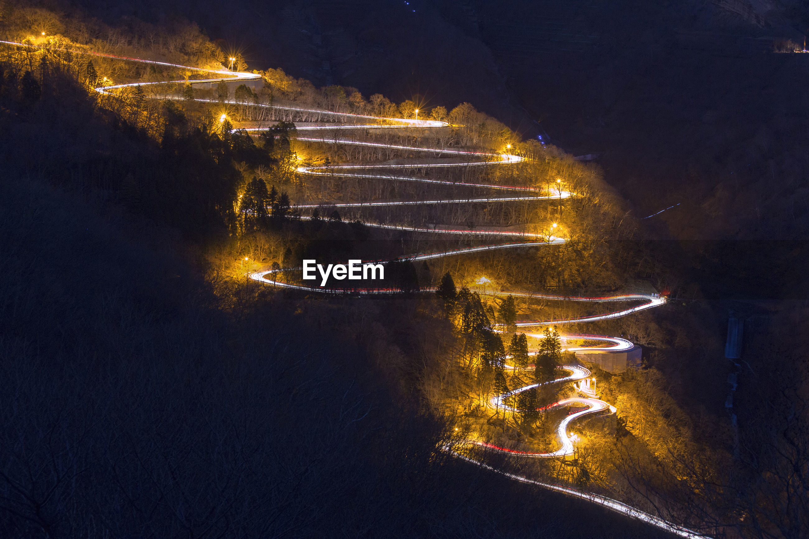 HIGH ANGLE VIEW OF ILLUMINATED CITY BY ROAD