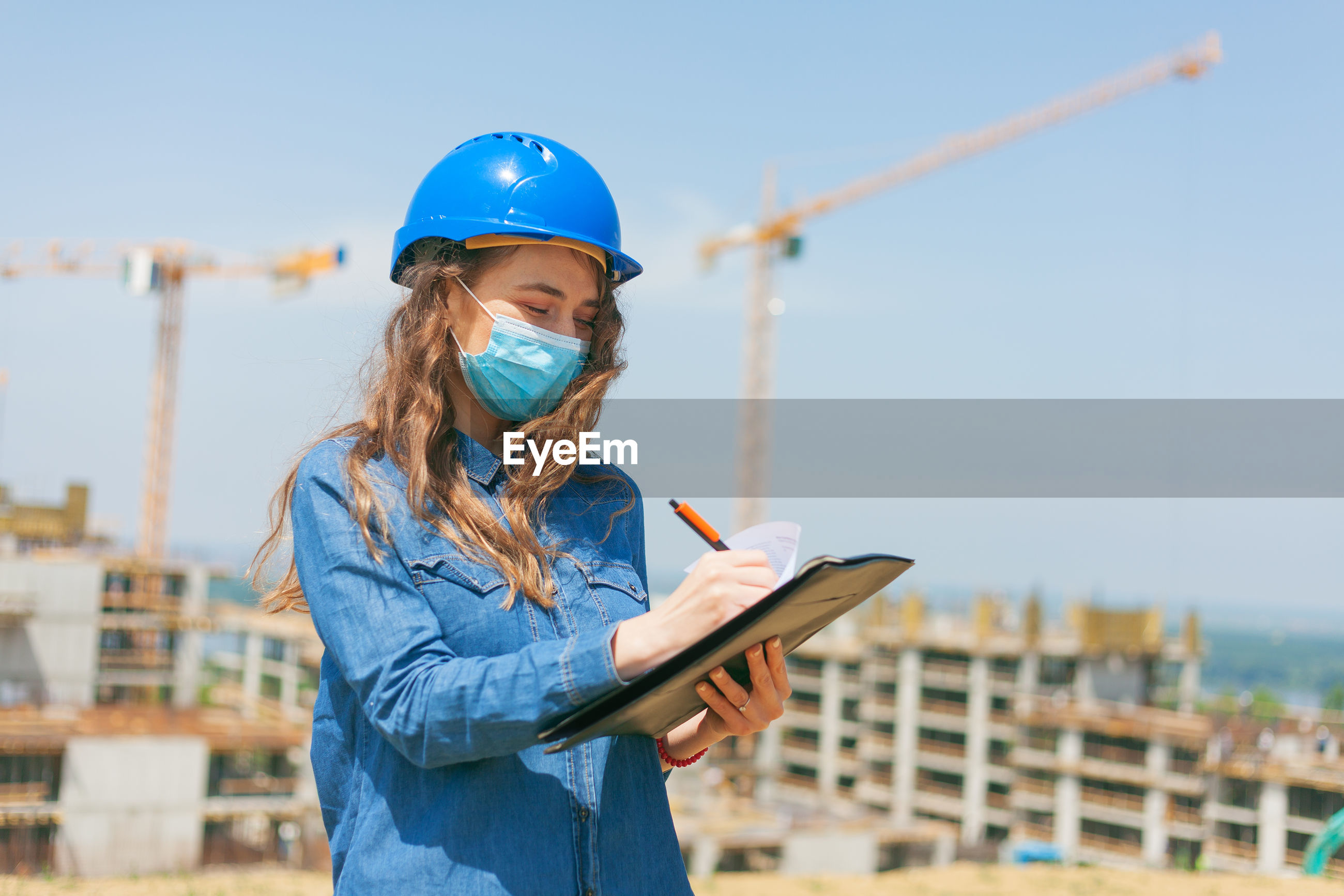 YOUNG WOMAN USING SMART PHONE WHILE STANDING AT CONSTRUCTION SITE