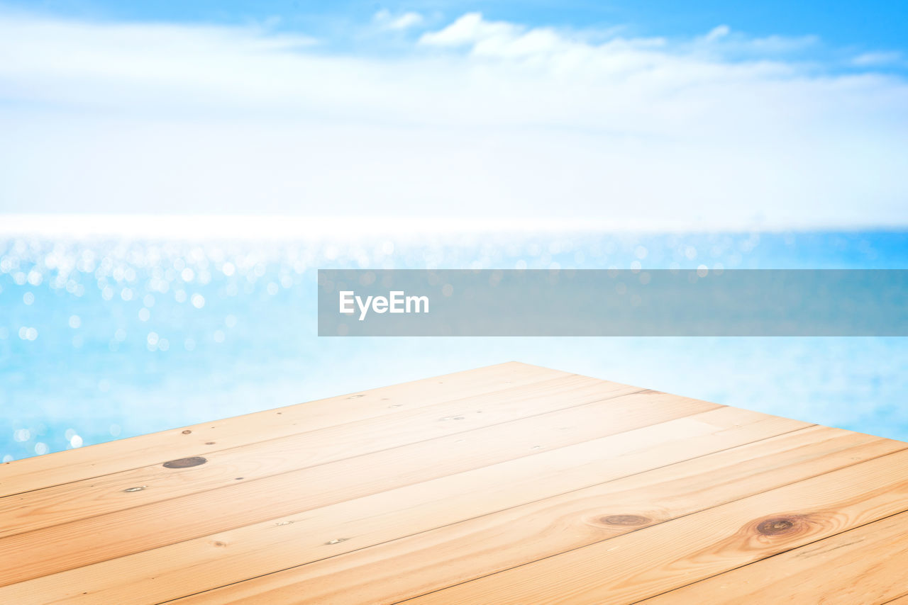 water, sea, sky, wood - material, nature, horizon, no people, day, horizon over water, beauty in nature, outdoors, focus on foreground, tranquility, scenics - nature, cloud - sky, land, blue, wood, table, swimming pool