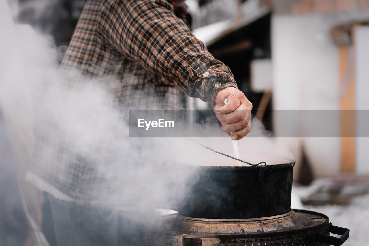 Midsection of man working on barbecue grill