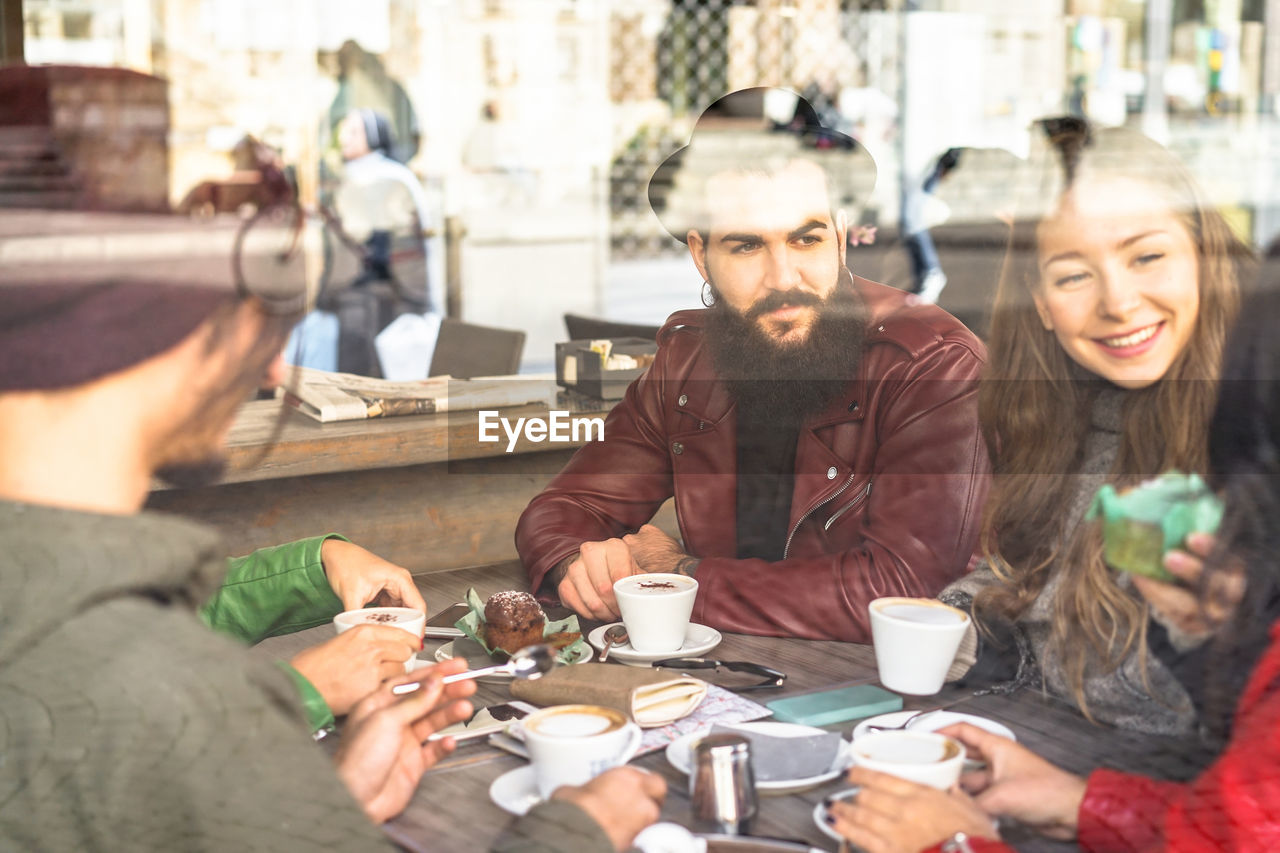 Friends Having Coffee At Table In Cafe