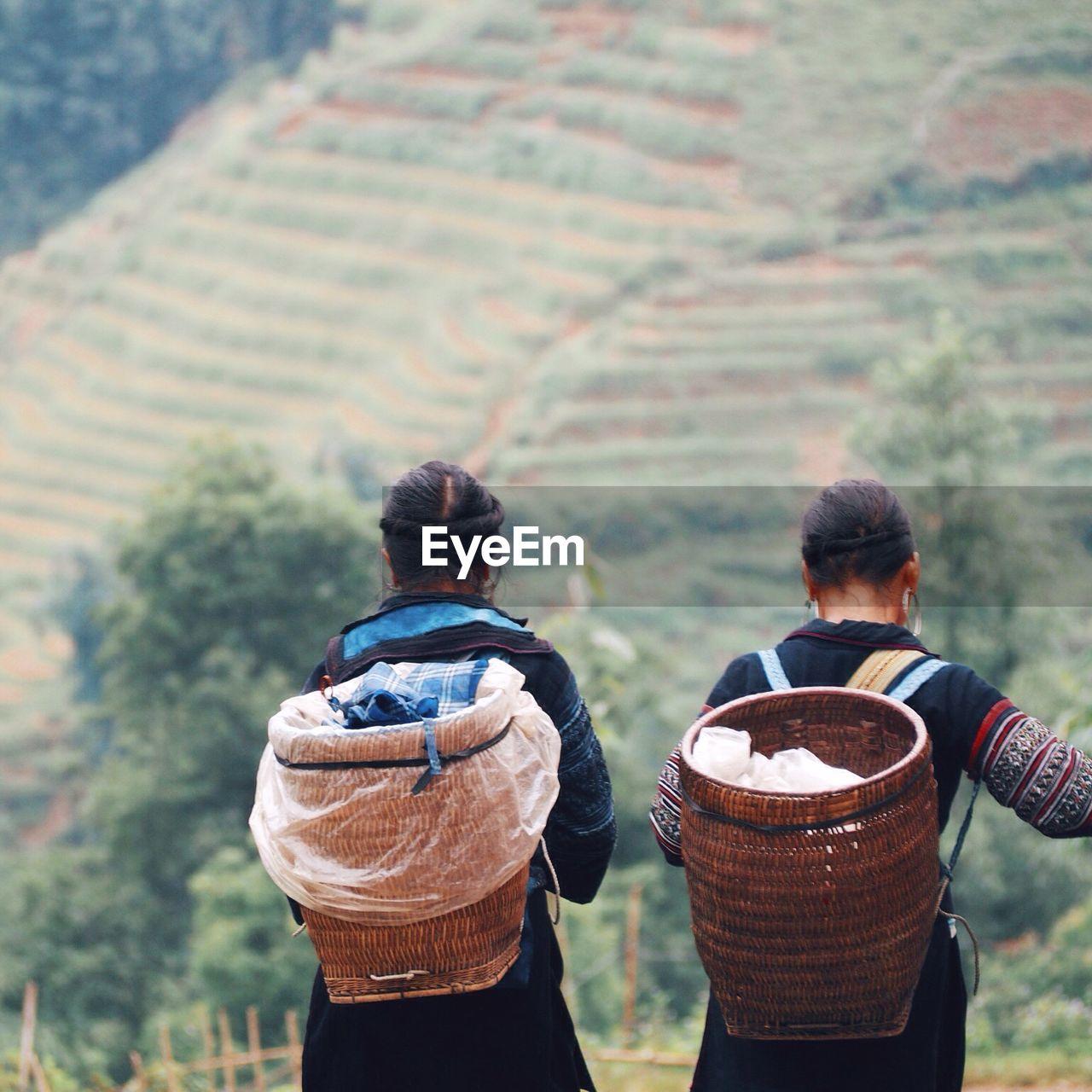 Rear View Of Women With Wicker Baskets On Field By Mountain