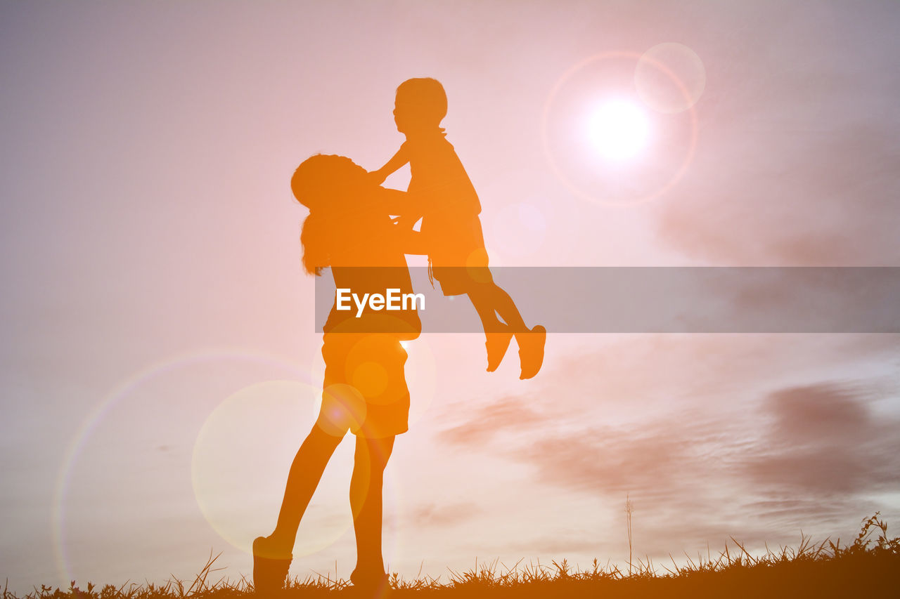 Mother Picking Up Son Against Cloudy Sky During Sunset
