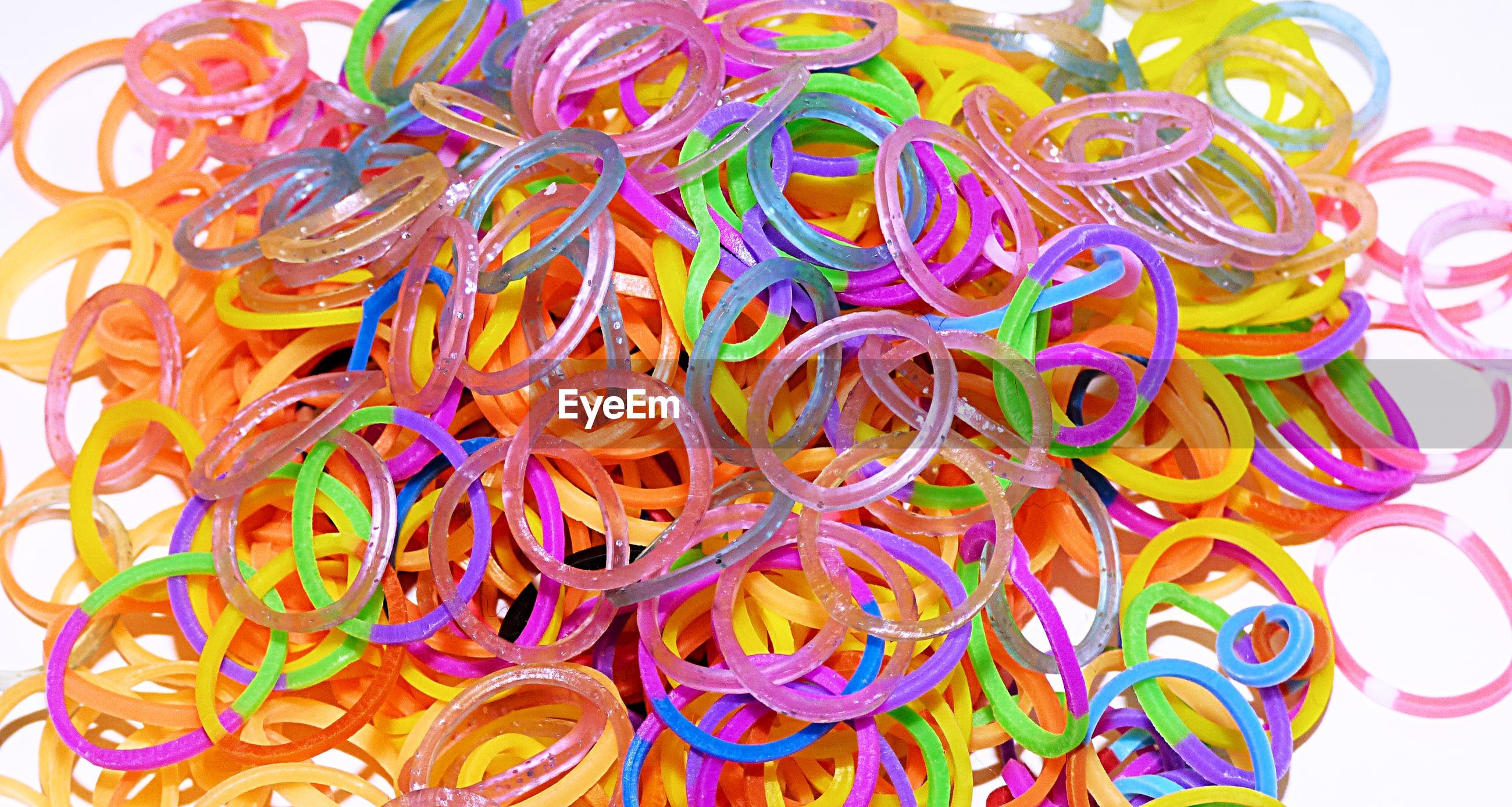 High angle view of colorful rubber bands on white background