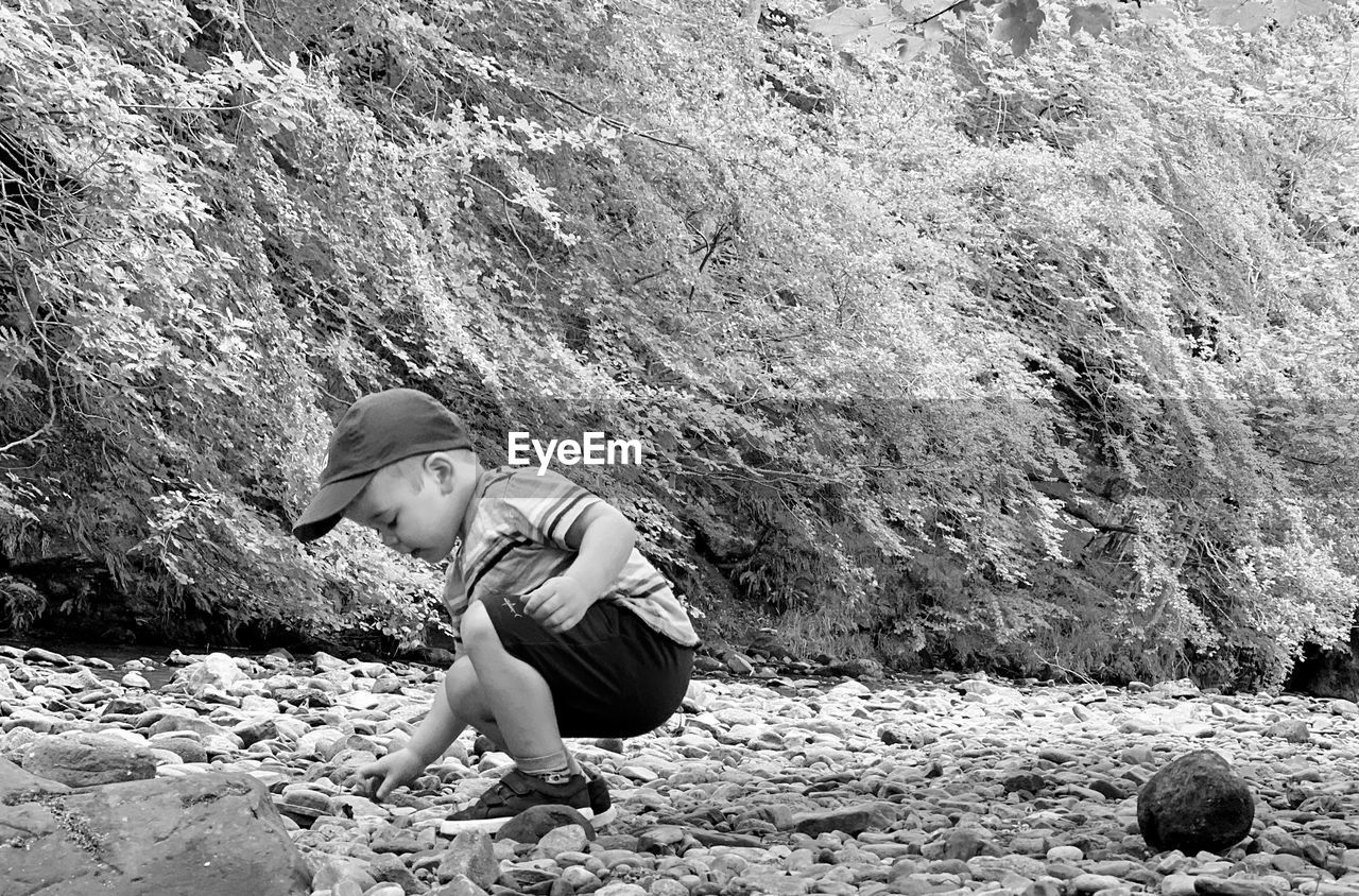 SIDE VIEW OF CHILD ON ROCK