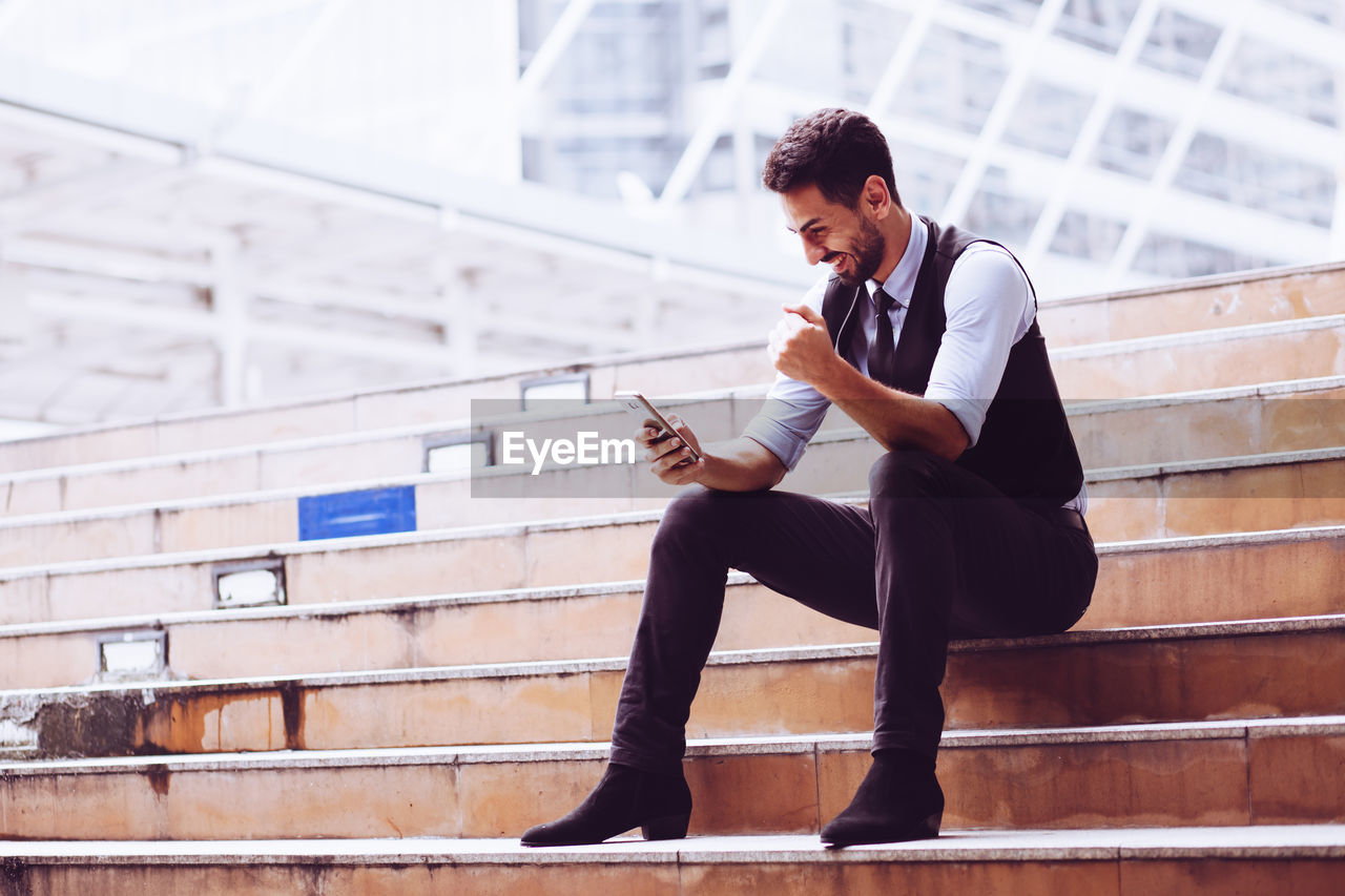 Full length of businessman using mobile phone while sitting on staircase