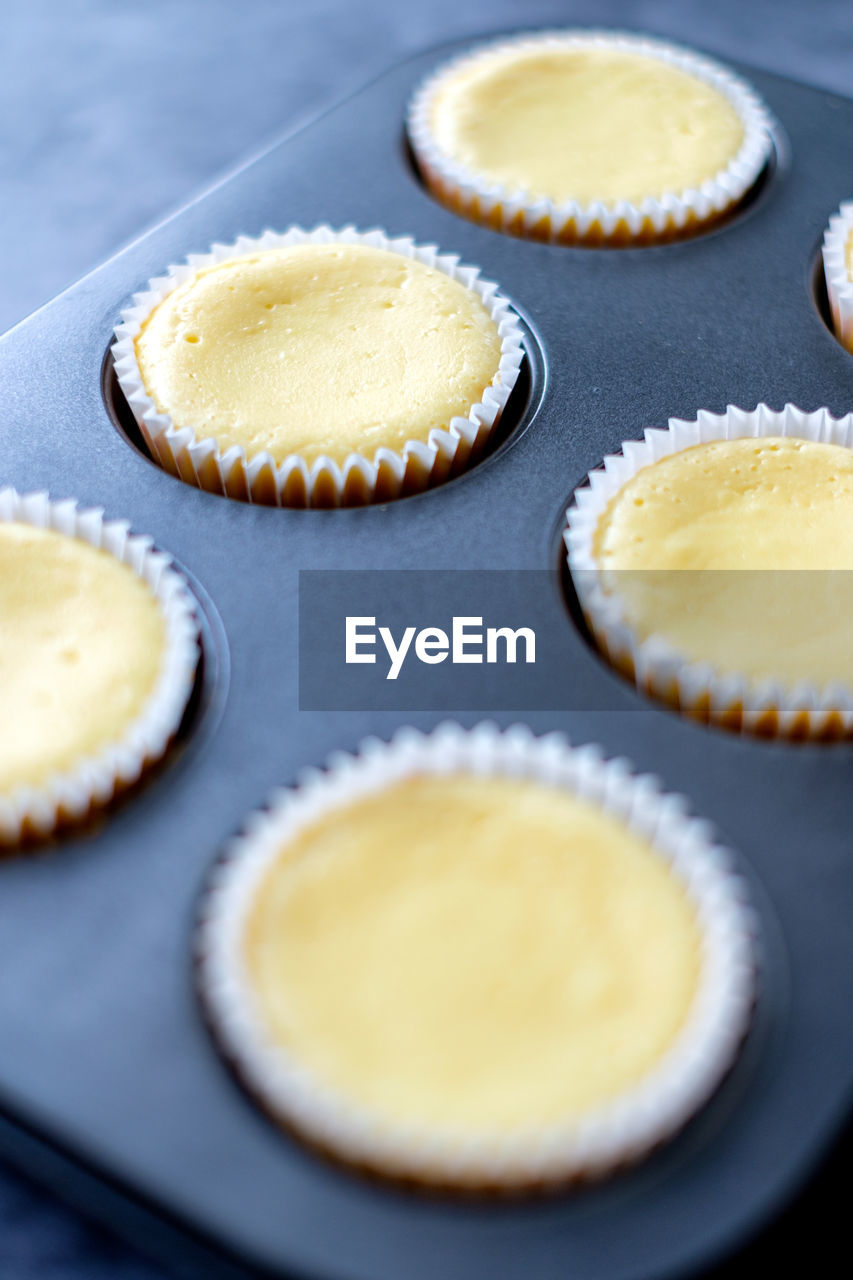 sweet food, cupcake, food and drink, sweet, cake, dessert, food, indoors, still life, freshness, indulgence, table, no people, unhealthy eating, temptation, baked, cupcake holder, preparation, yellow, selective focus, preparing food, baking sheet, muffin, snack