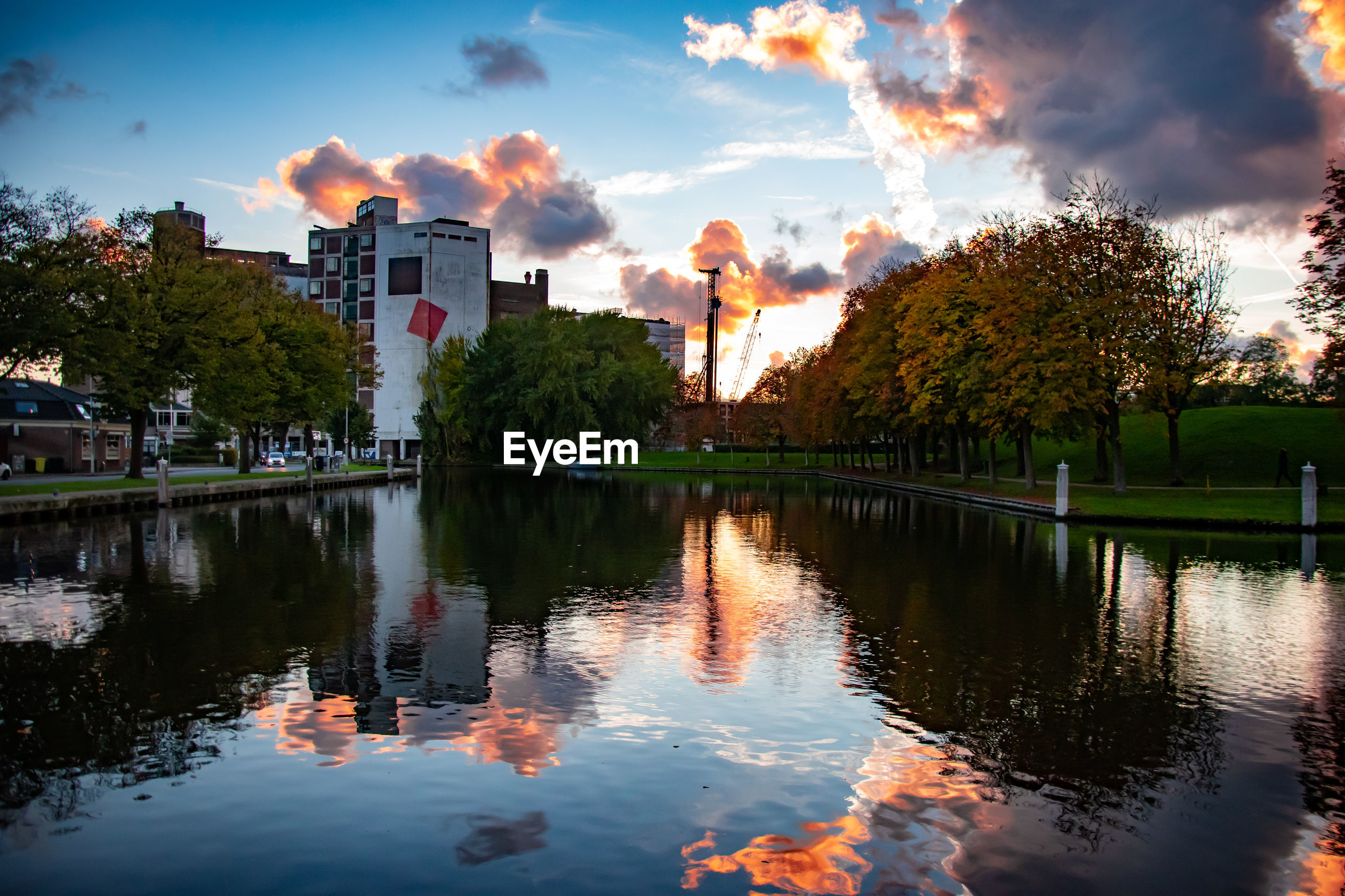 Reflection of trees and buildings in lake during sunset