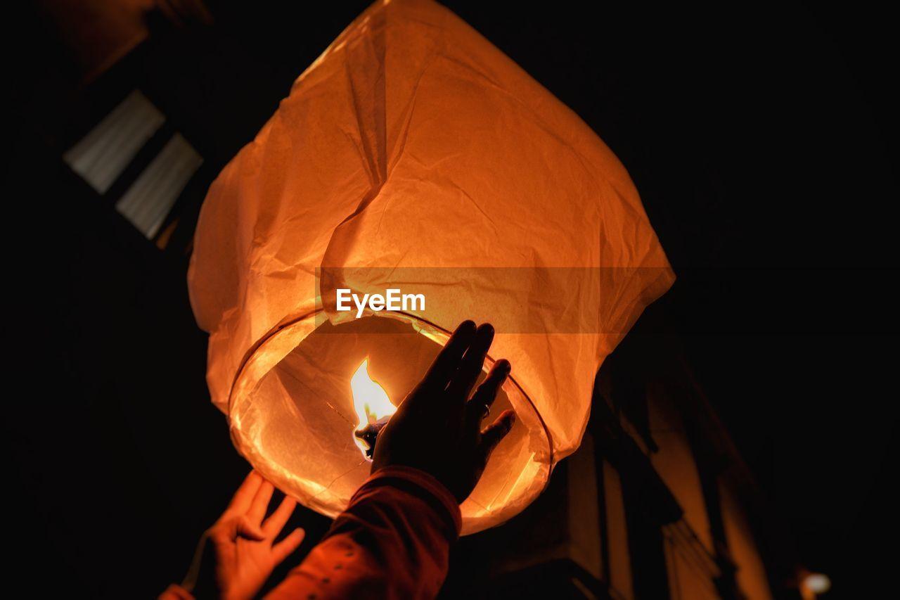 Cropped Hand Holding Illuminated Paper Lantern At Night