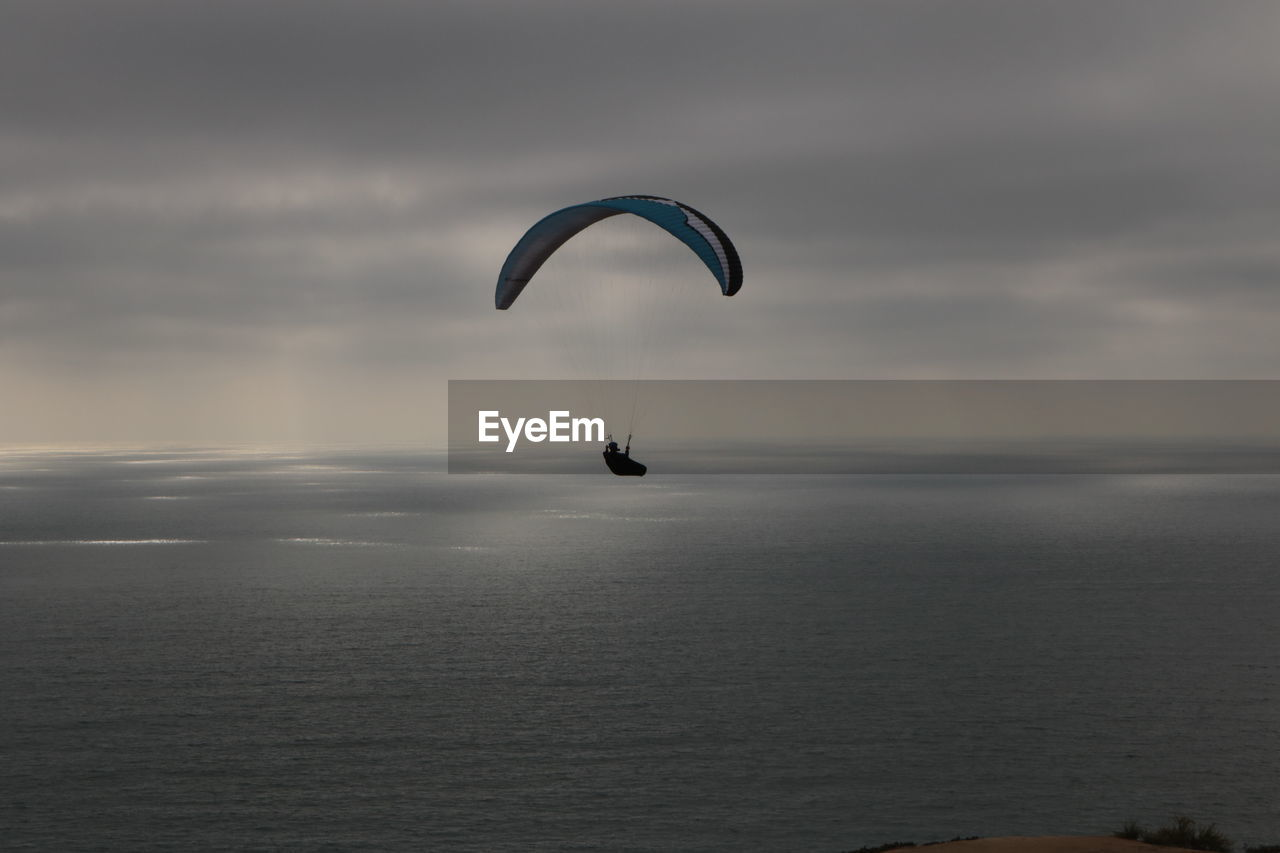Silhouette Person Paragliding Over Sea Against Sky