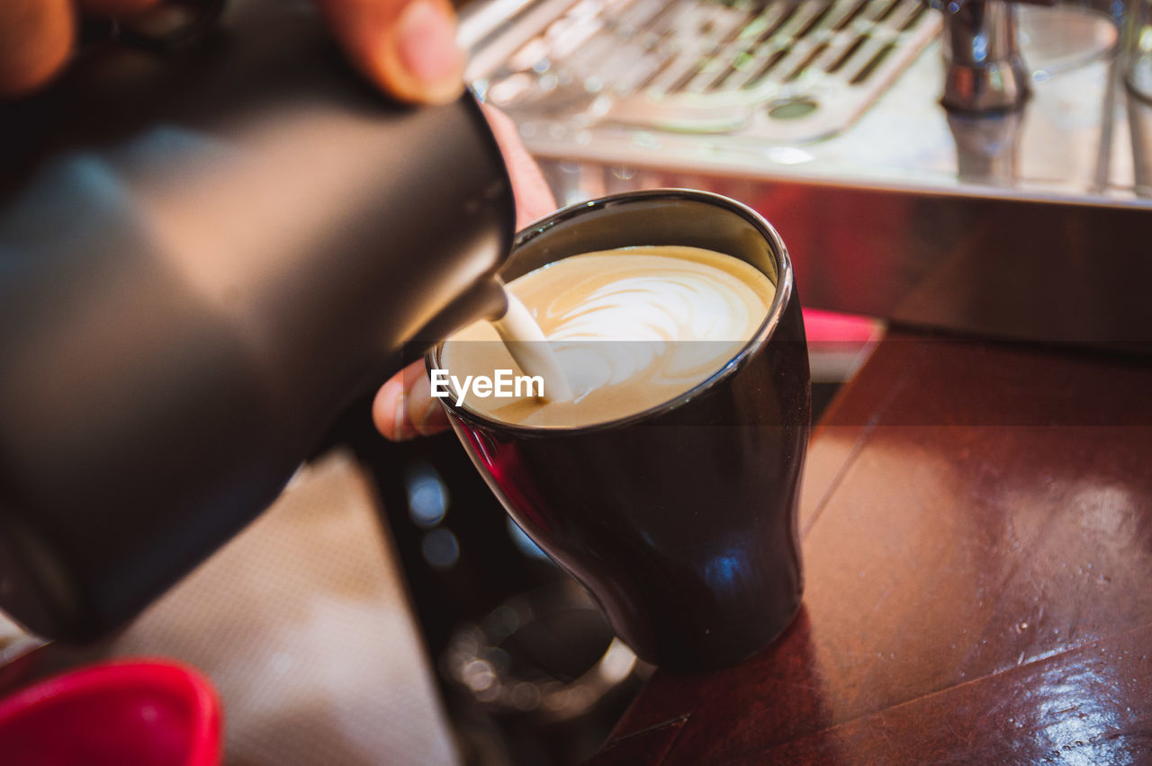 Close-Up Of Barista Pouring Cream In Coffee Cup At Cafe