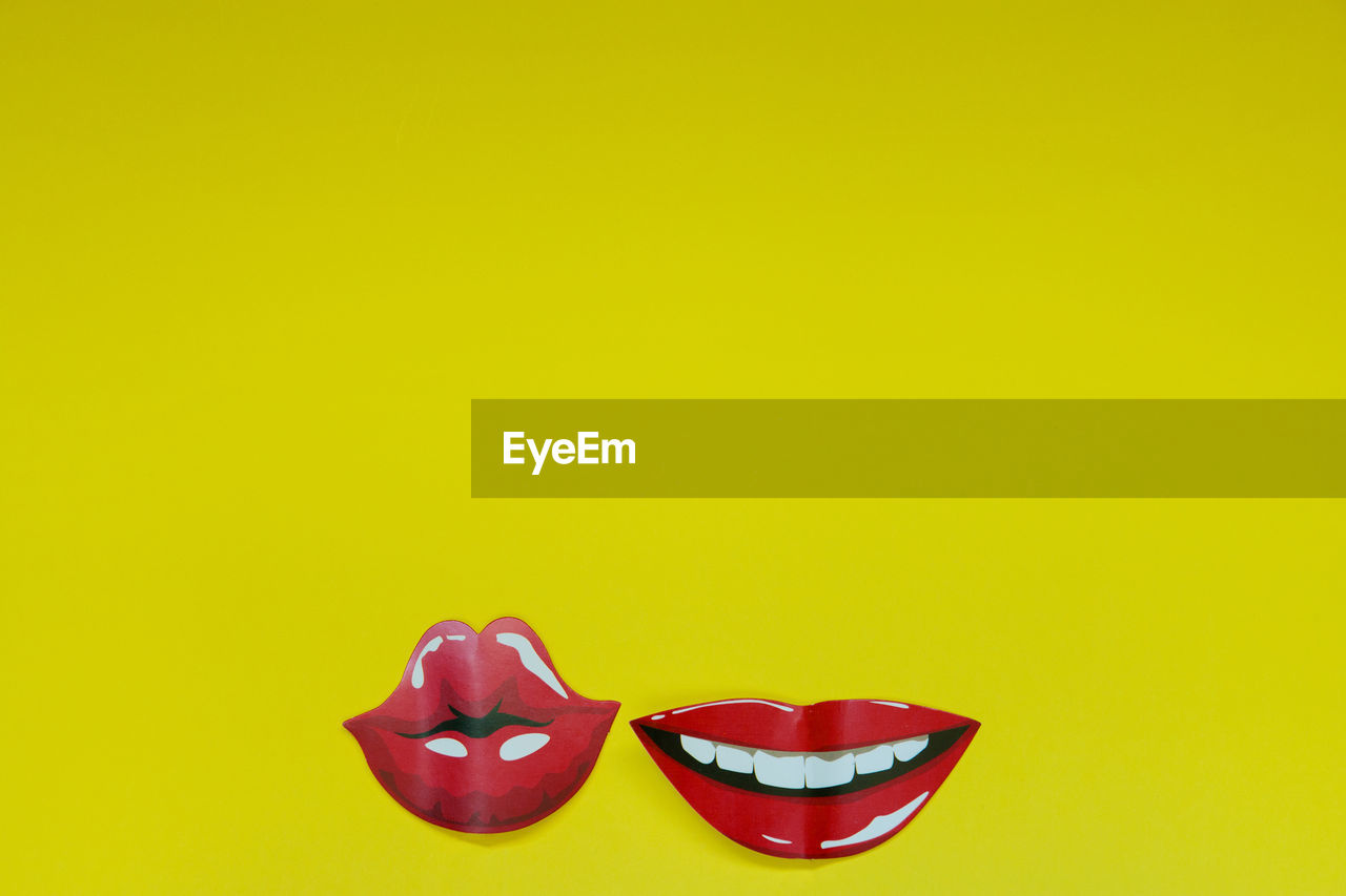 Illustrative Image Of Red Lips Against Yellow Background