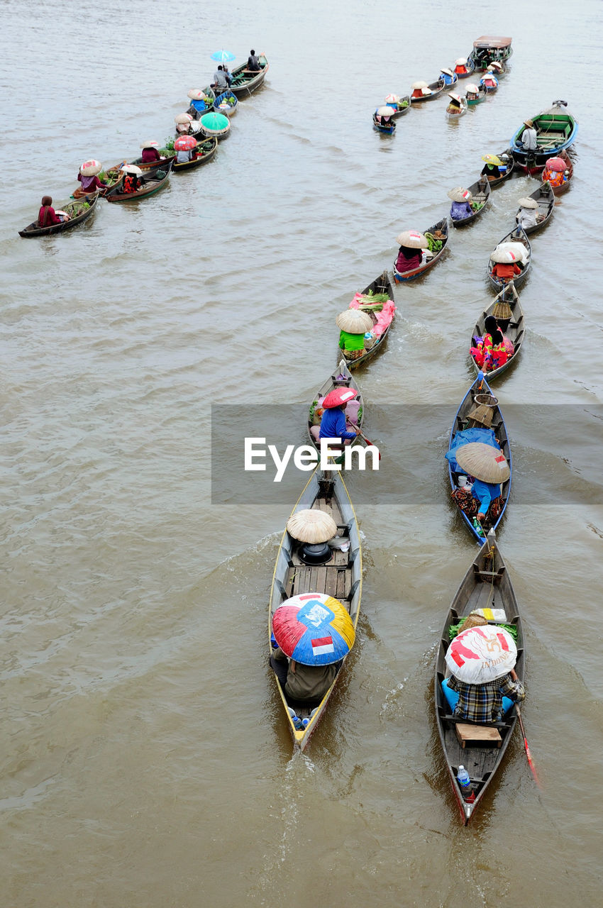 High Angle View Of People Traveling In Boats Sailing On River