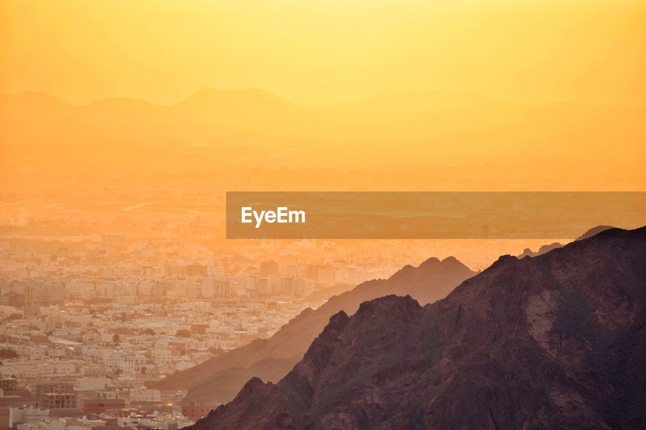 mountain, beauty in nature, sky, scenics - nature, sunset, nature, tranquility, mountain range, tranquil scene, orange color, no people, landscape, environment, idyllic, non-urban scene, outdoors, silhouette, high angle view, cityscape