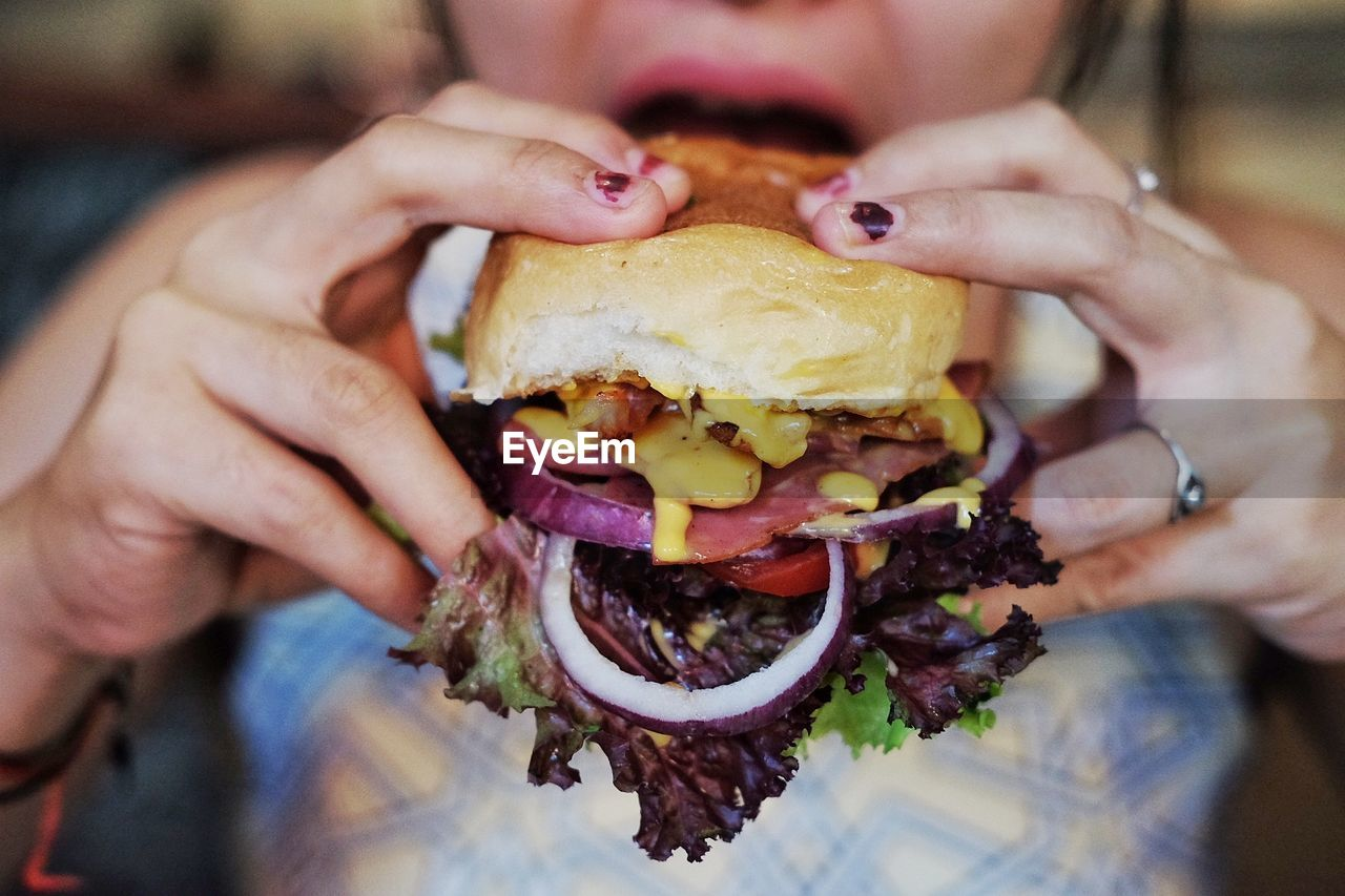 Midsection Of Woman Having Burger