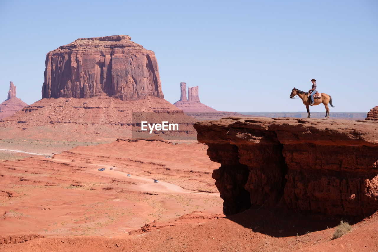 Woman riding horse on mountain against clear sky during sunny day