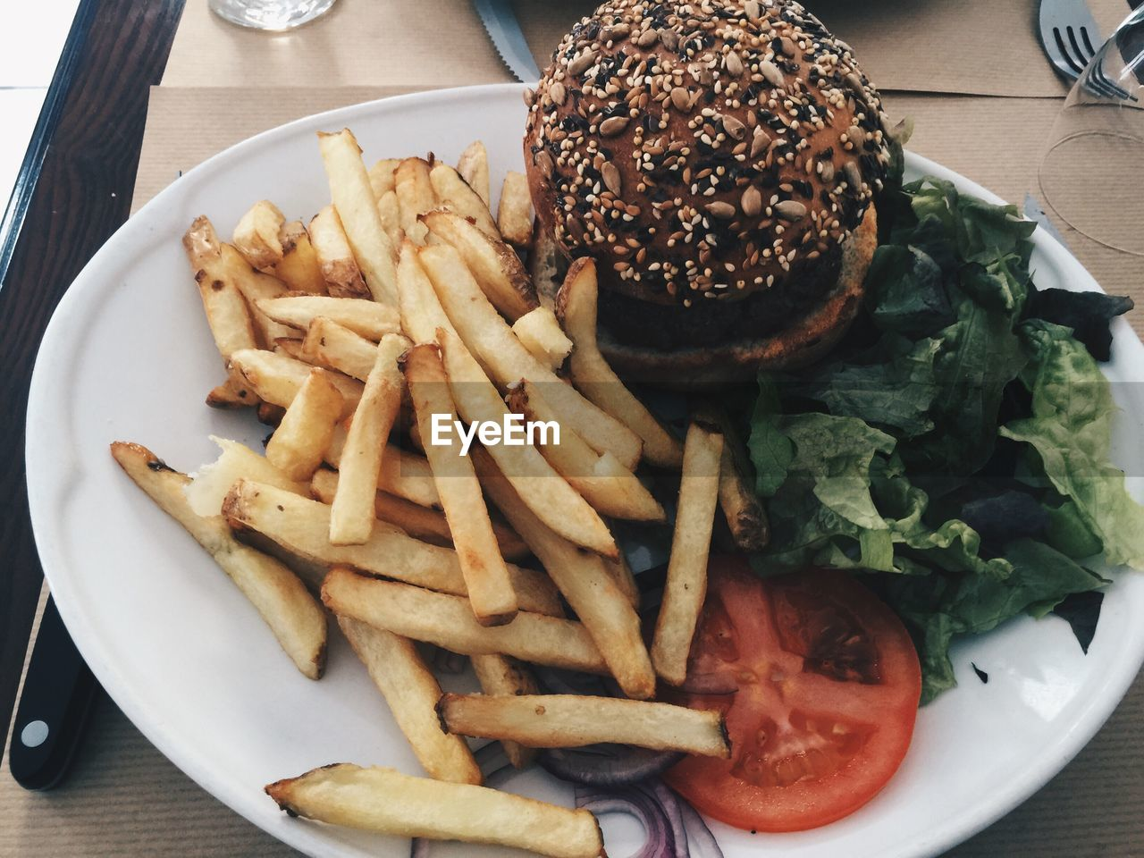 High Angle View Of Burger And French Fries In Plate On Table
