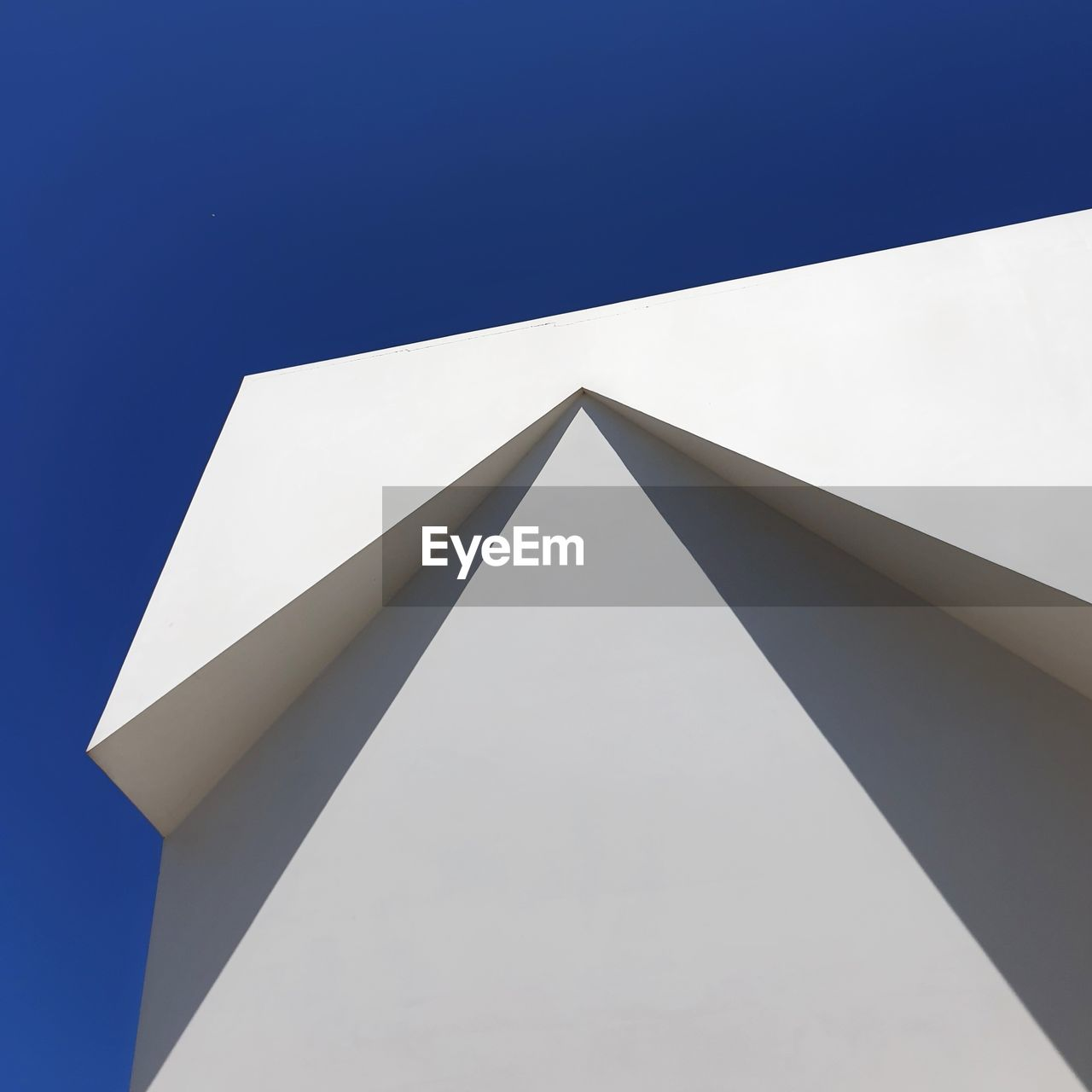 low angle view, no people, architecture, sky, built structure, clear sky, nature, day, building exterior, copy space, white color, blue, sunlight, geometric shape, outdoors, triangle shape, shape, building, pattern, design, angle