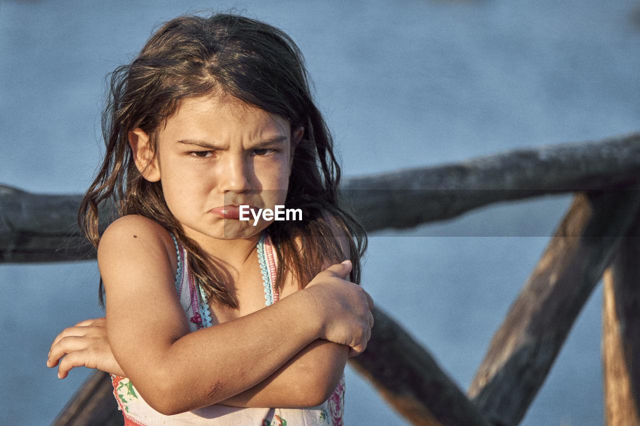 Portrait Of Sad Girl Standing Against Railing