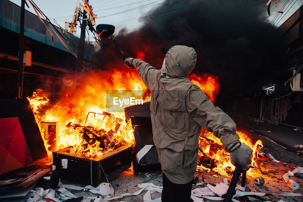 Man throwing cap in fire on street