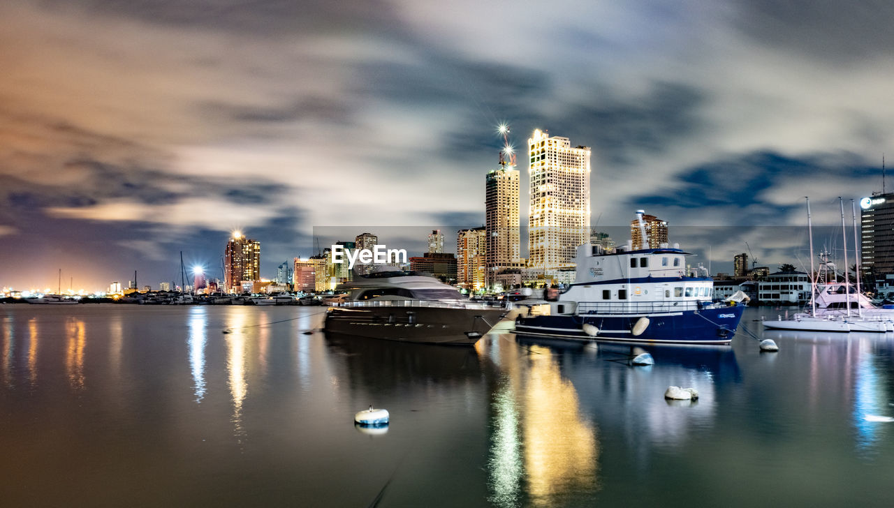 building exterior, water, built structure, architecture, city, sky, nautical vessel, cloud - sky, building, reflection, office building exterior, transportation, skyscraper, illuminated, cityscape, waterfront, urban skyline, nature, modern, no people, tall - high, outdoors, yacht, bay, sailboat