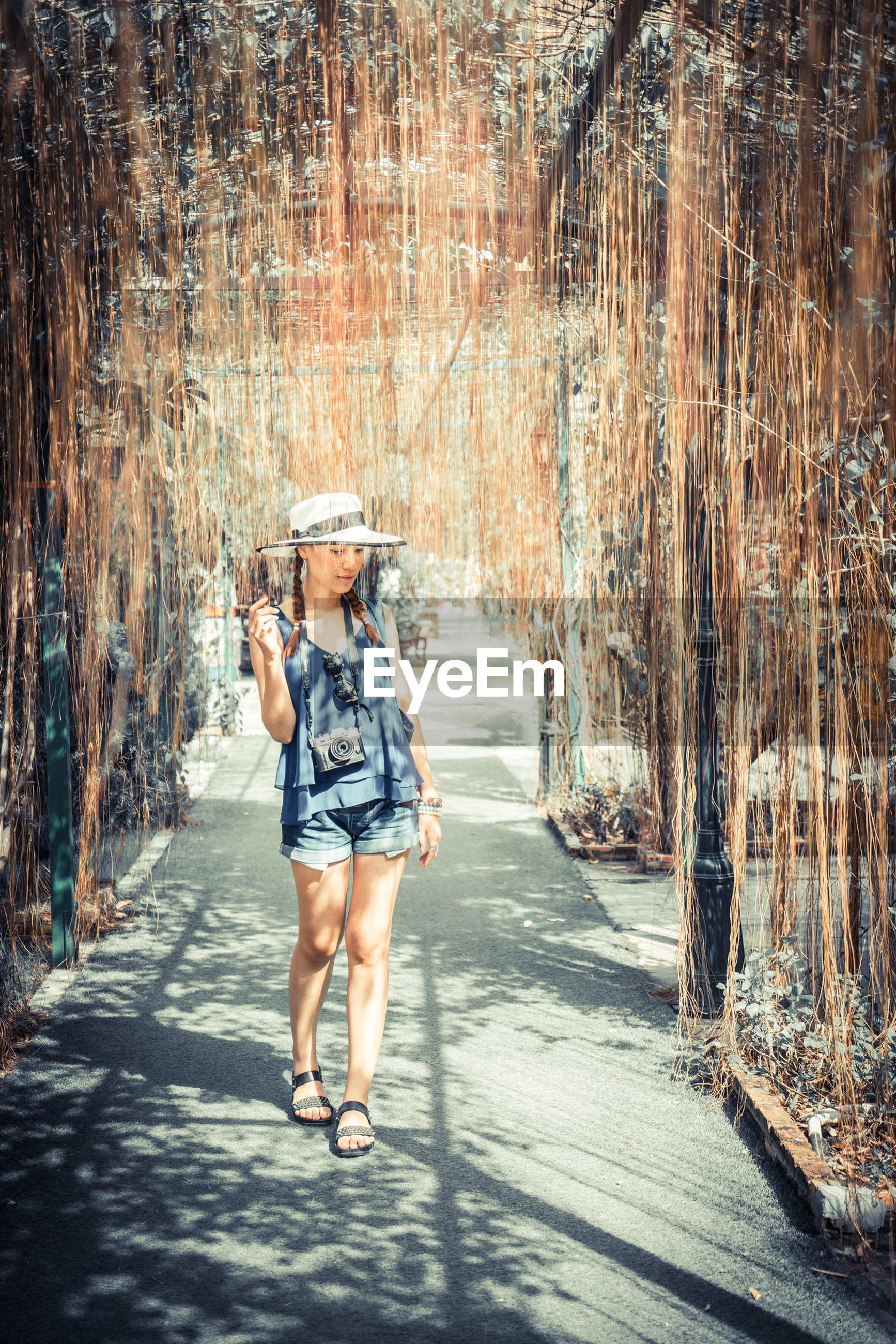 Woman walking on walkway amidst dry vines