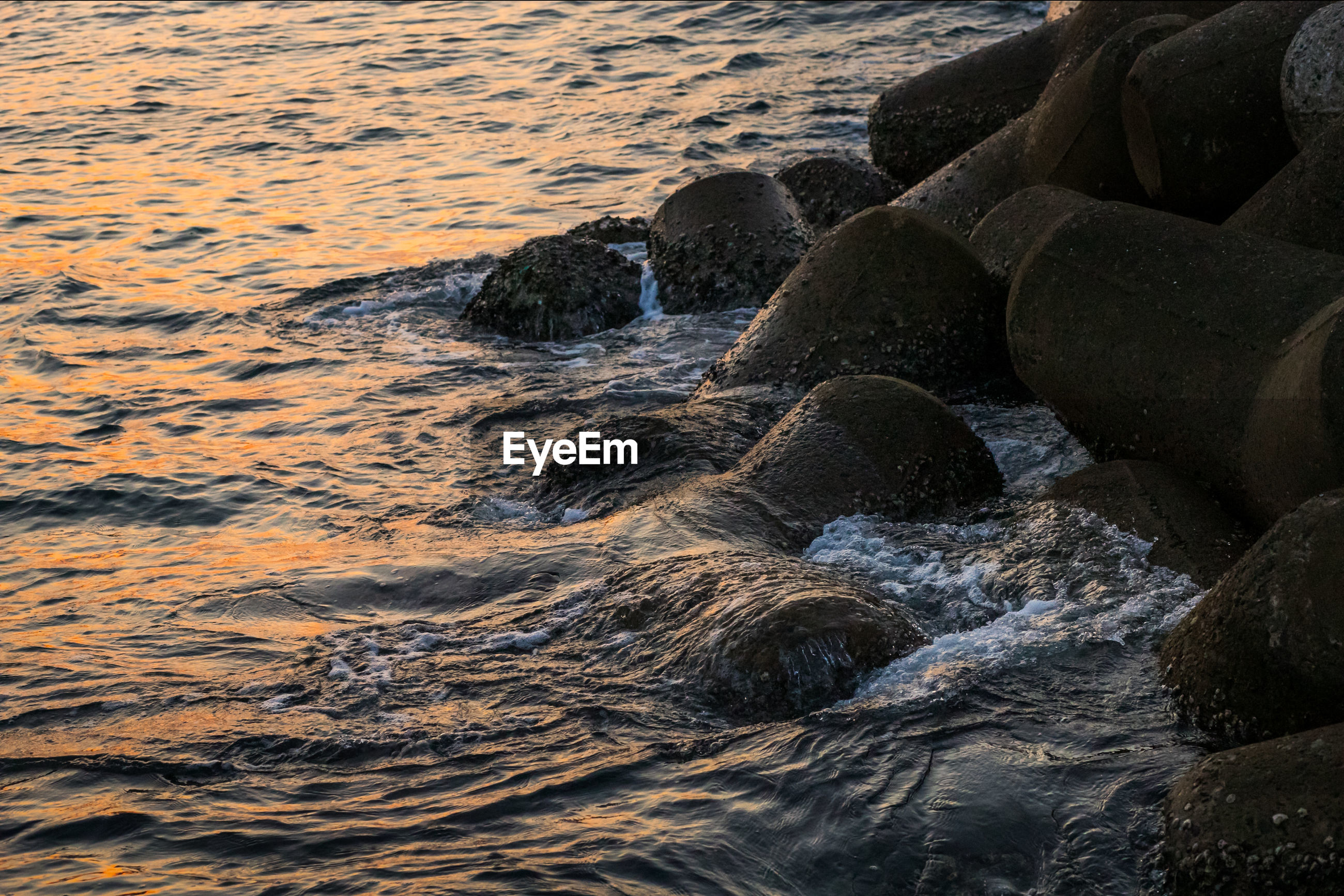 Tetrapods in sea during sunset
