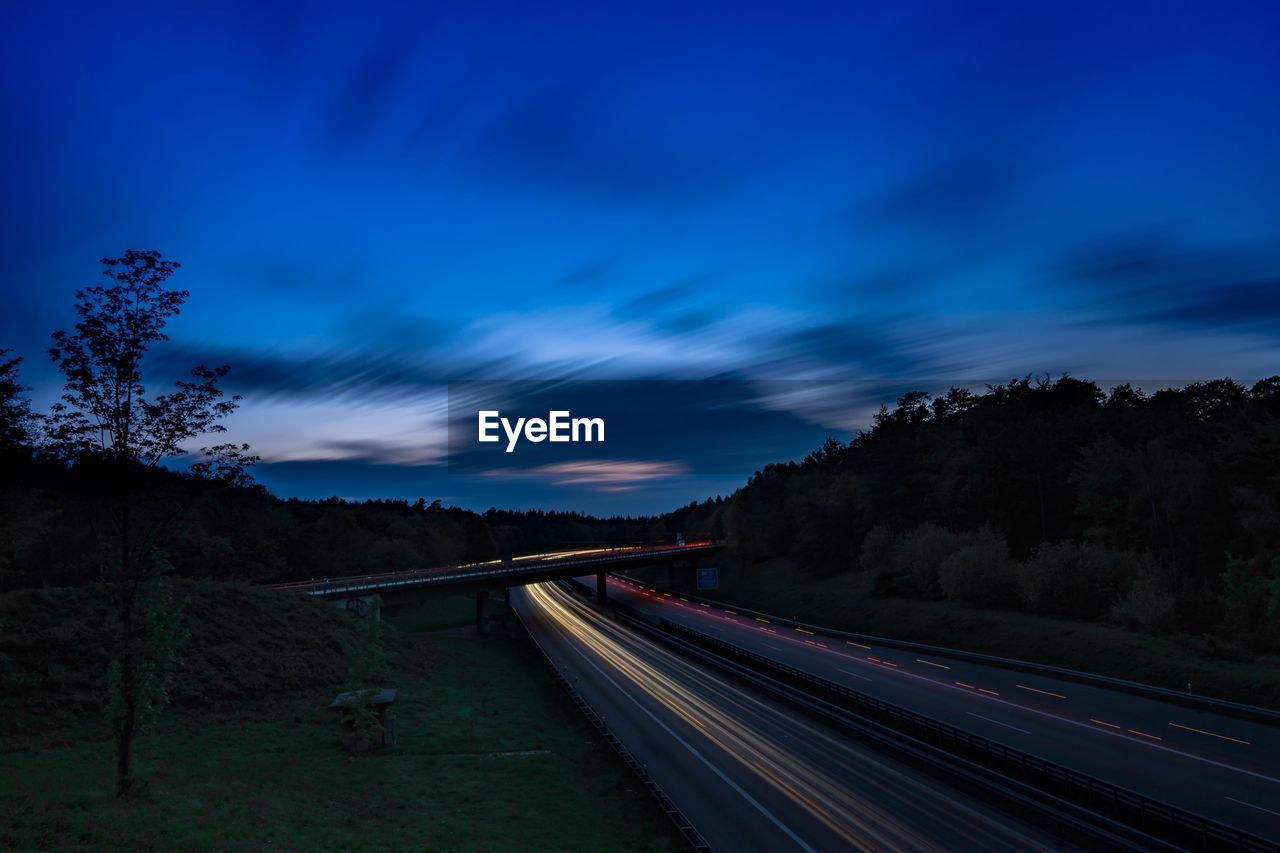sky, transportation, cloud - sky, long exposure, tree, motion, nature, blurred motion, plant, speed, light trail, road, no people, the way forward, blue, direction, connection, outdoors, night, beauty in nature