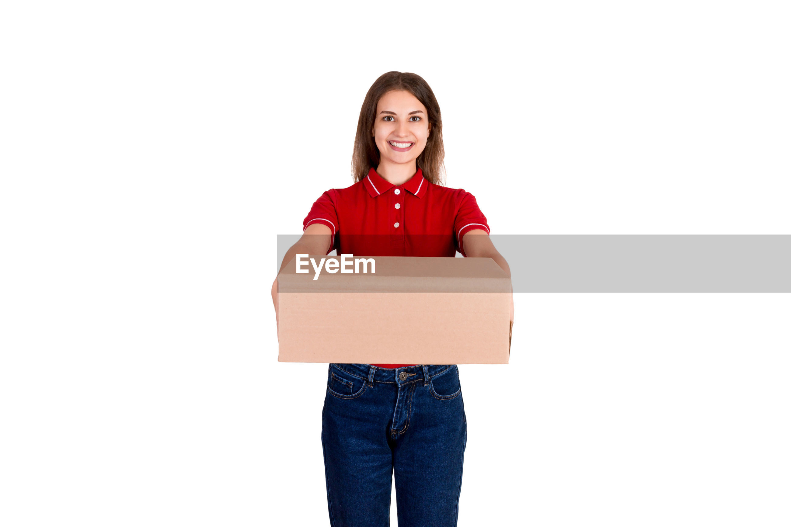 Portrait of smiling delivery woman holding package while standing against white background