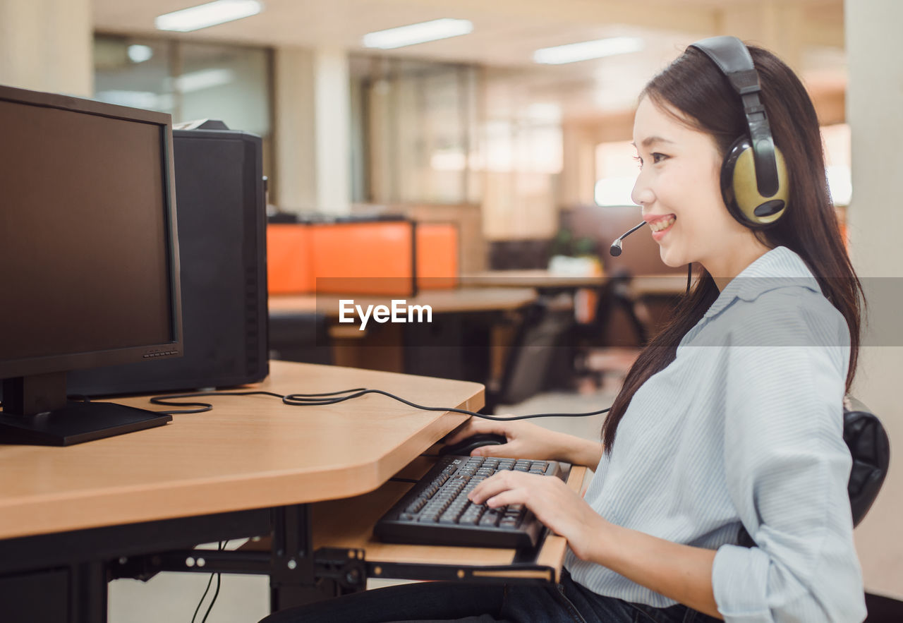 Smiling young customer service representative talking on headset