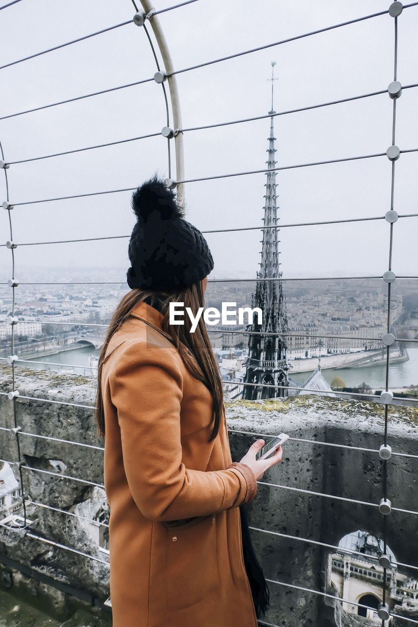 Side view of woman looking at tower from observation point in city during winter