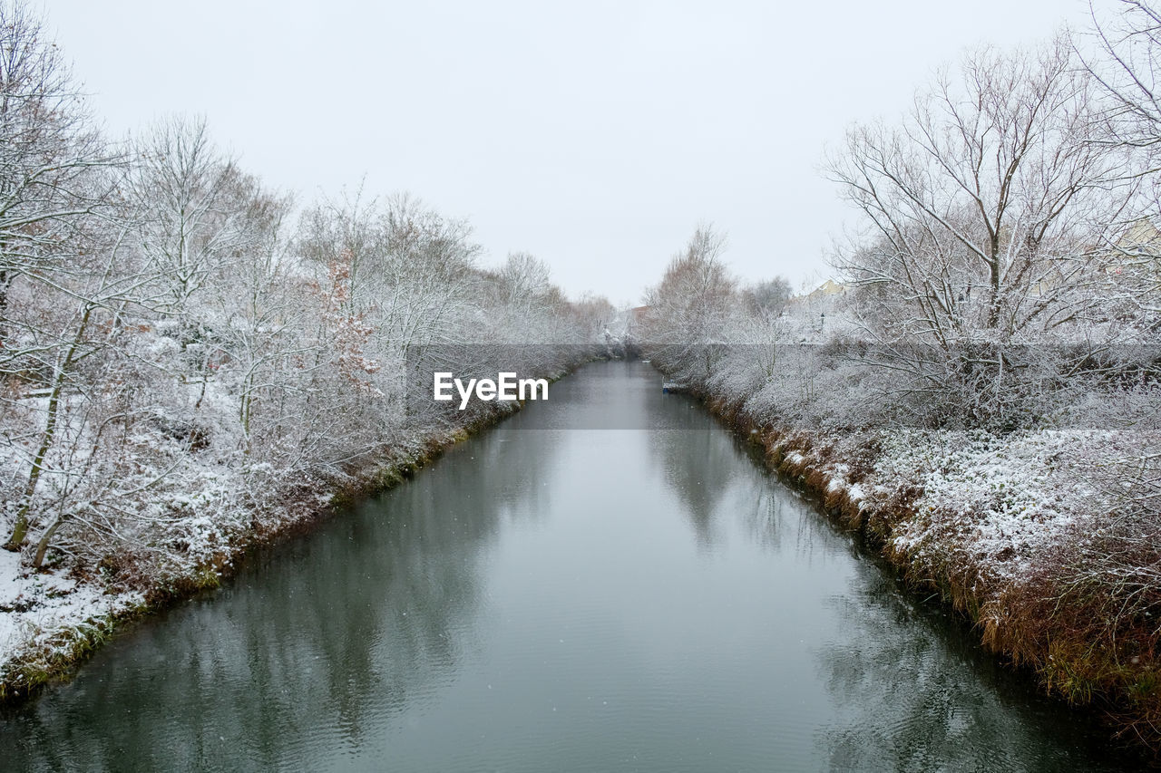 FROZEN RIVER AMIDST TREES AGAINST SKY